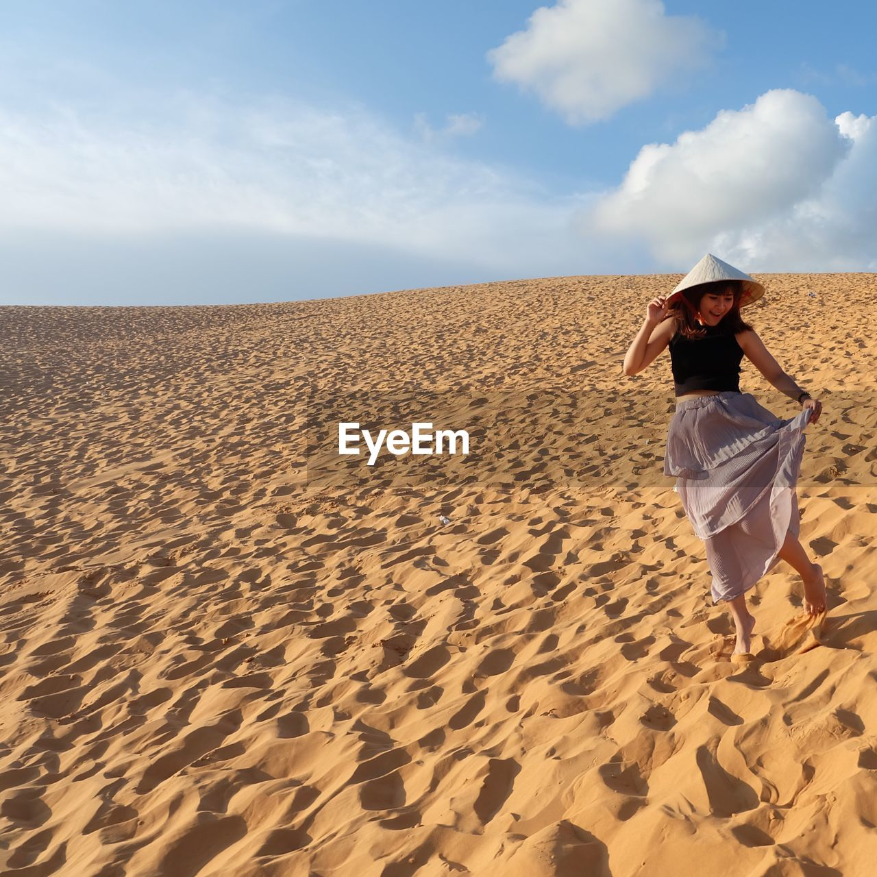 Young Woman Walking At Desert Against Sky