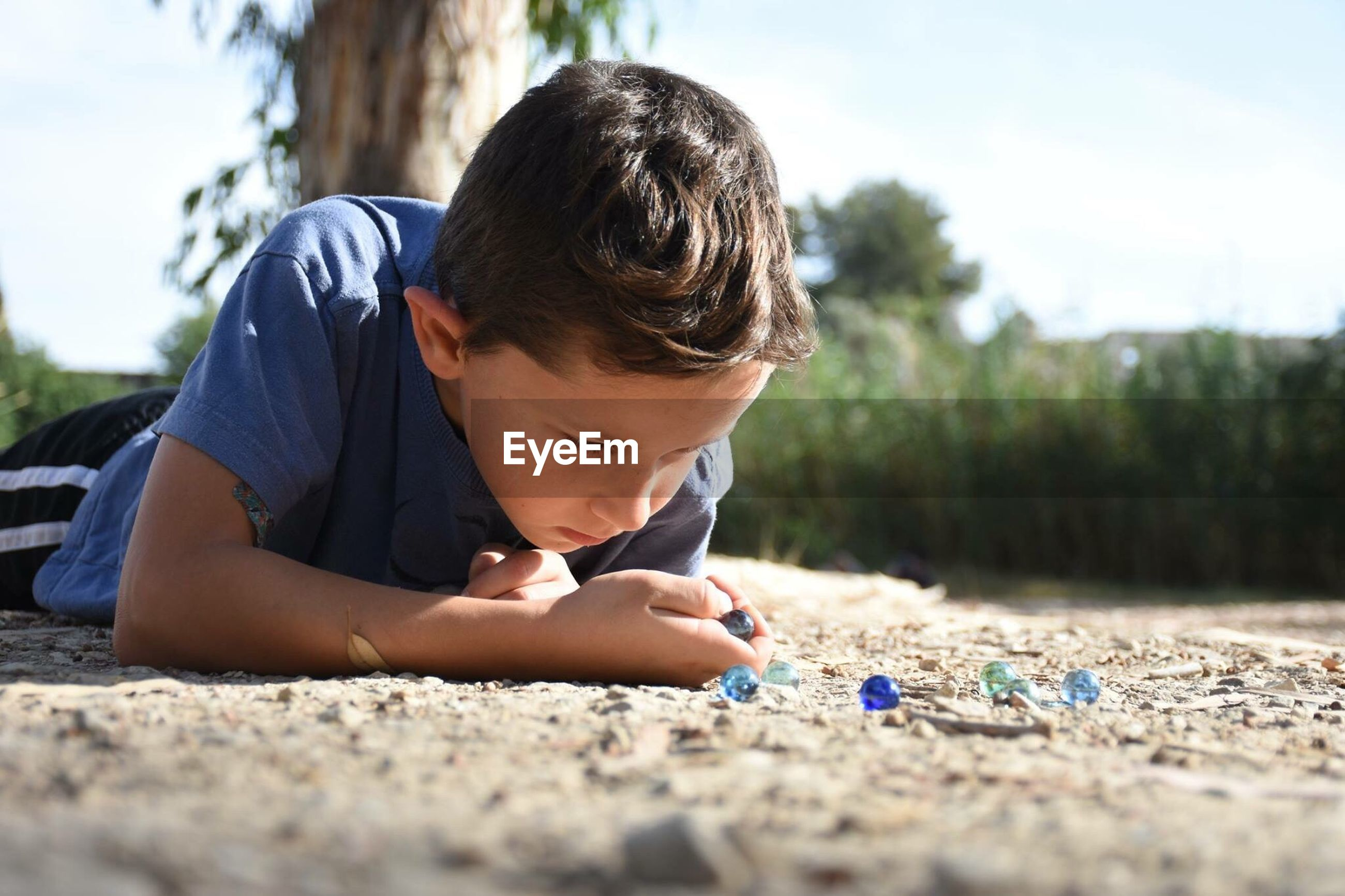 Boy playing marbles while laying on field