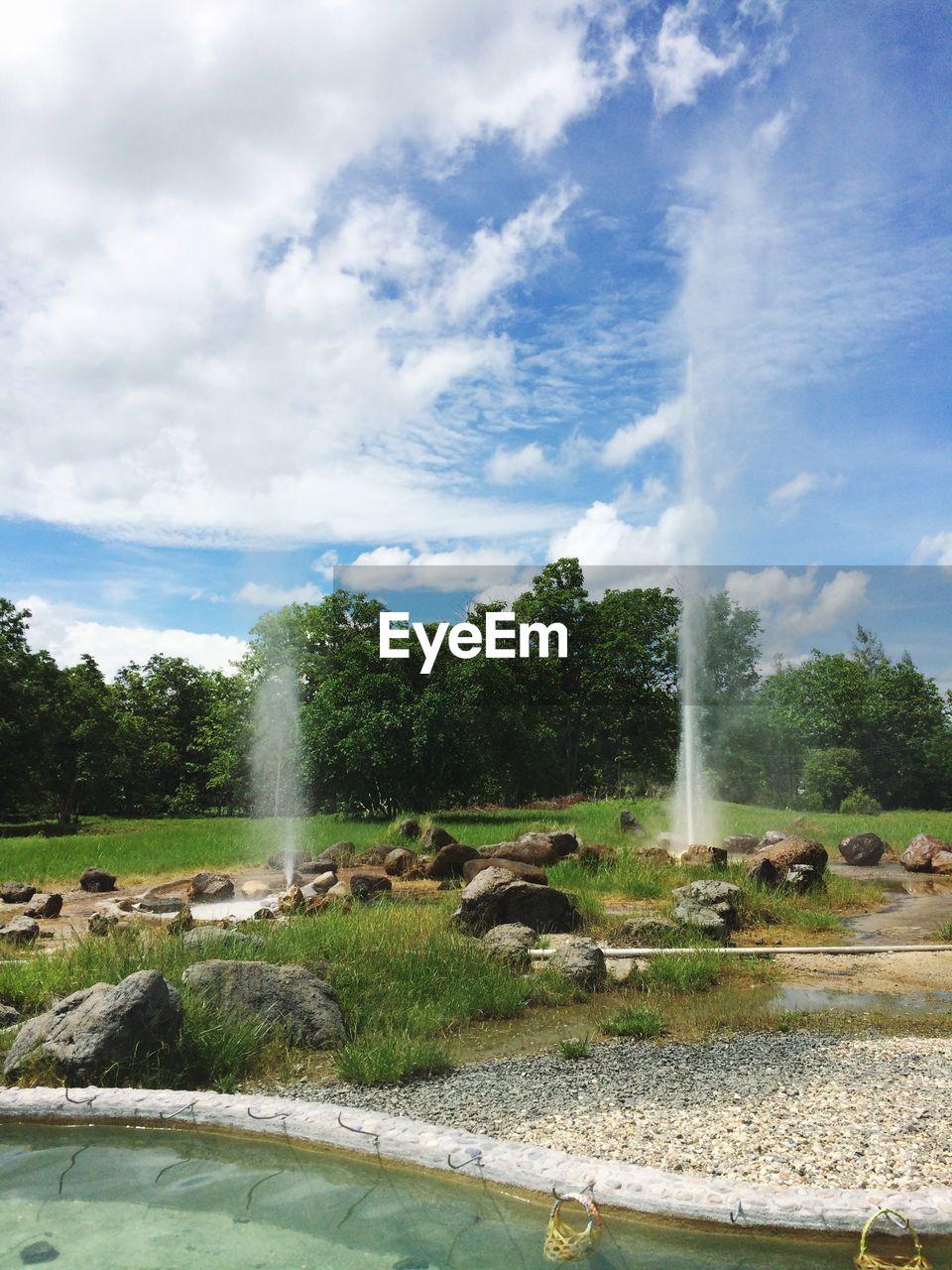Fountain against sky on field