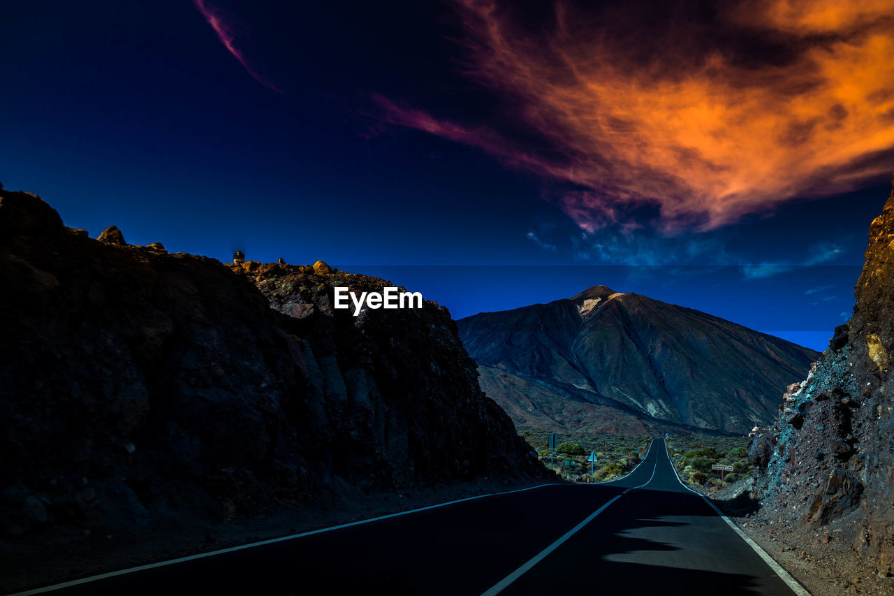 mountain, sky, scenics - nature, beauty in nature, cloud - sky, transportation, no people, nature, road, non-urban scene, tranquil scene, tranquility, blue, mountain range, environment, idyllic, landscape, outdoors, rock, rock - object, formation, mountain peak