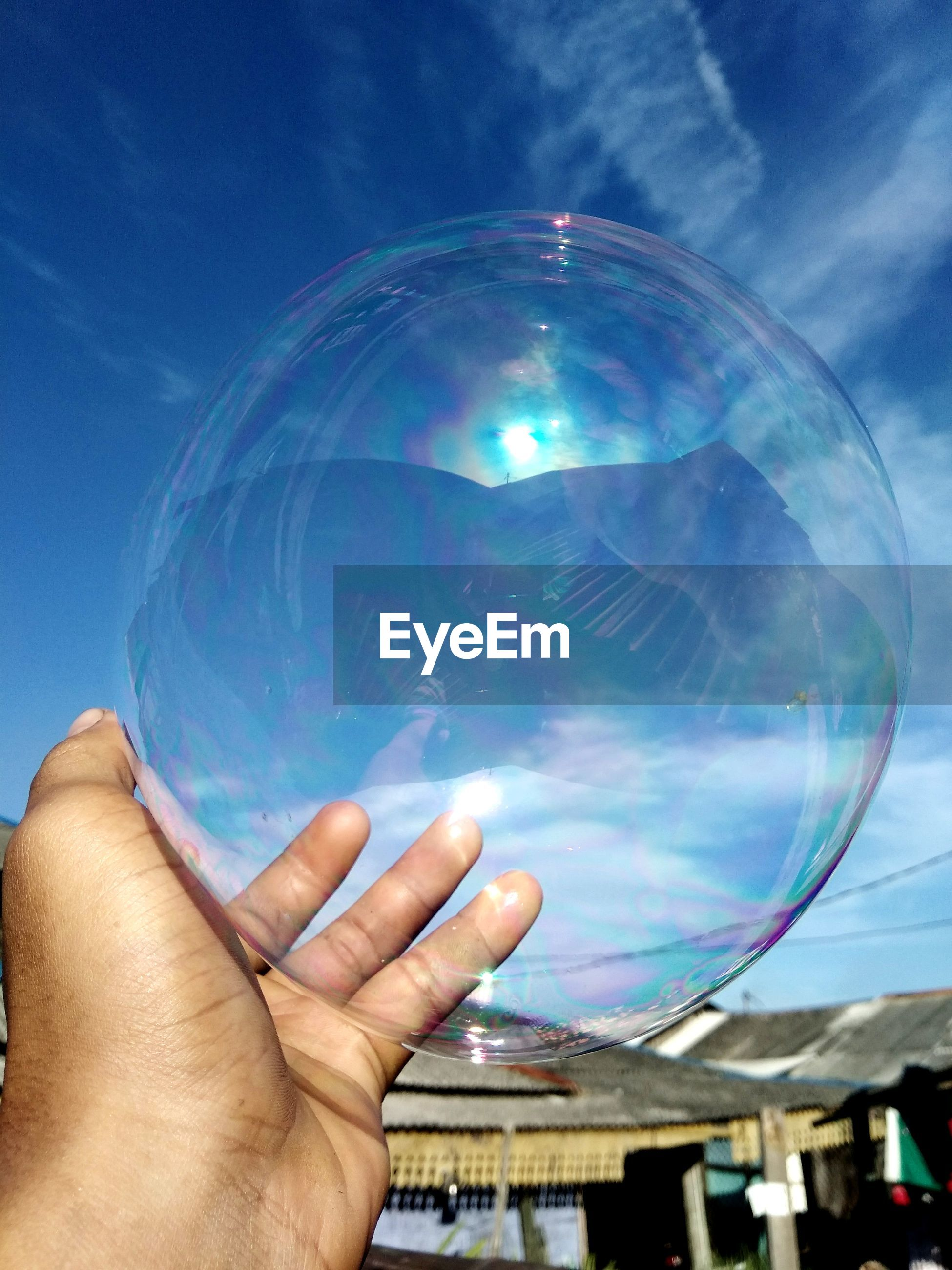 Cropped image of person hand holding bubble against sky