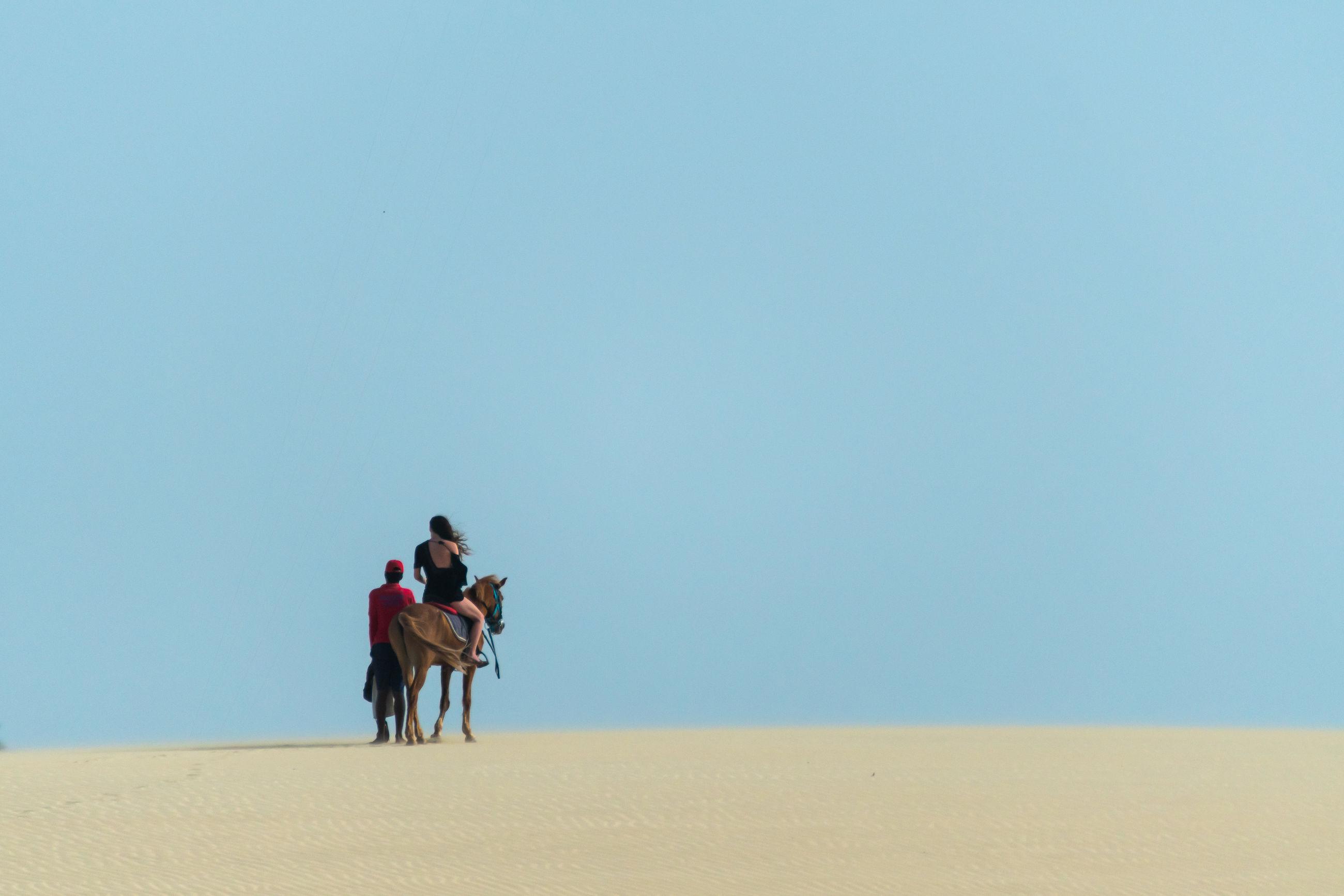 Men riding horse on desert against clear sky