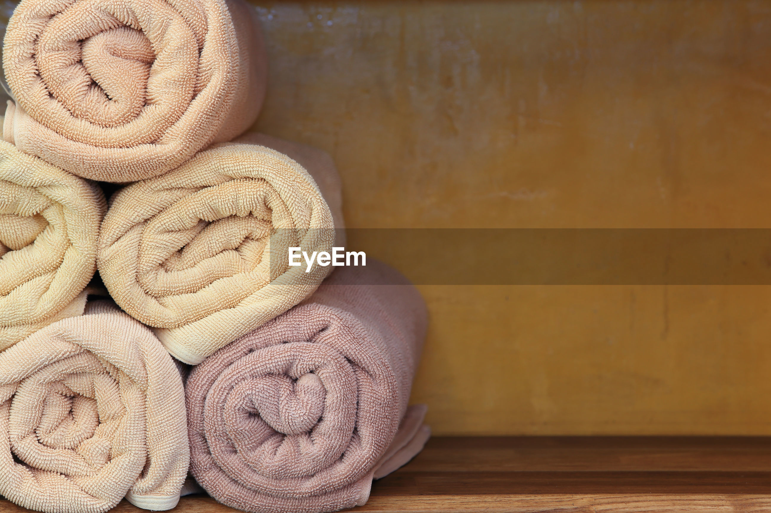 Close-up of rolled up towels on shelf at spa
