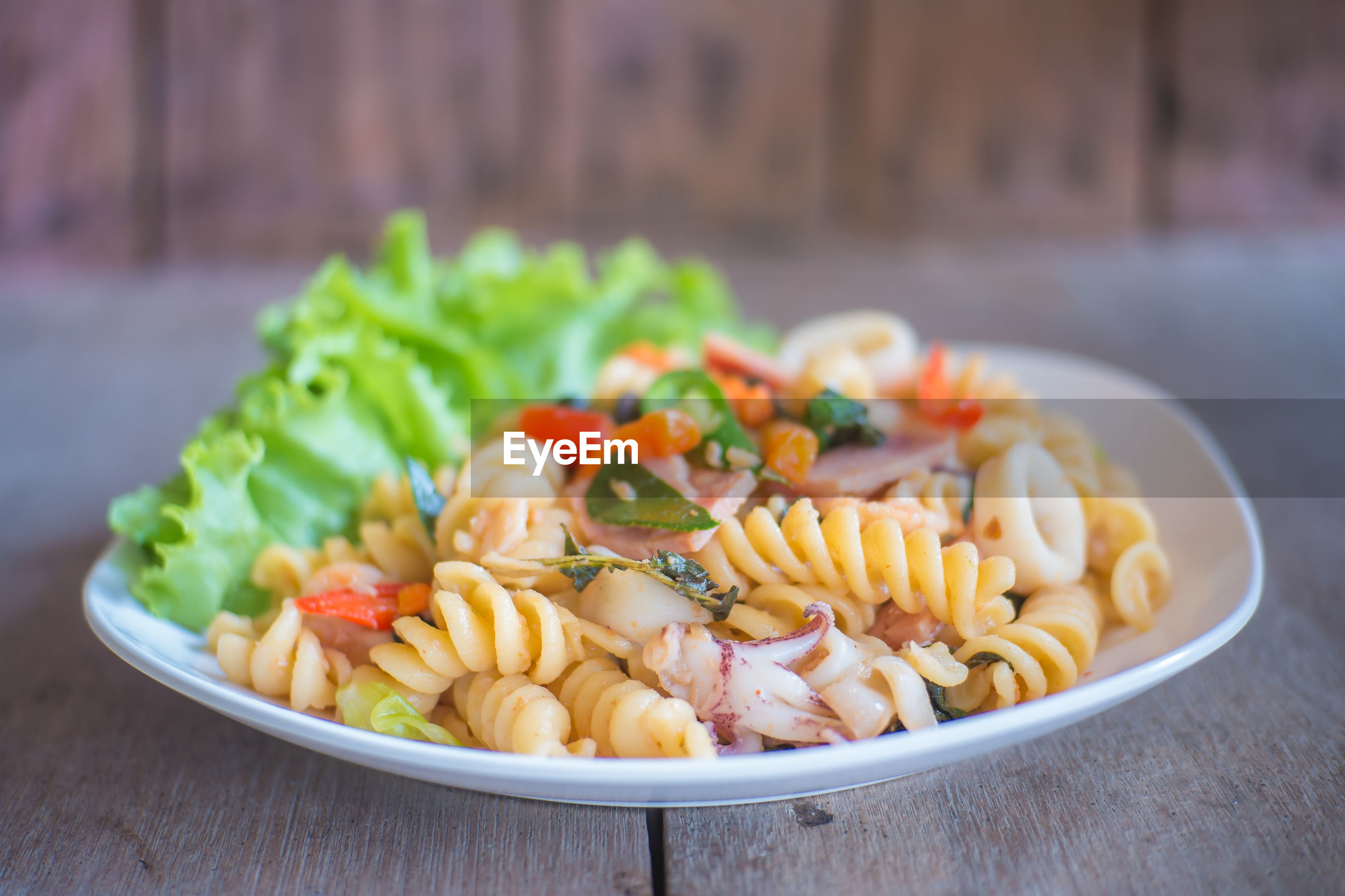 Close-up of pasta served in plate on wooden table