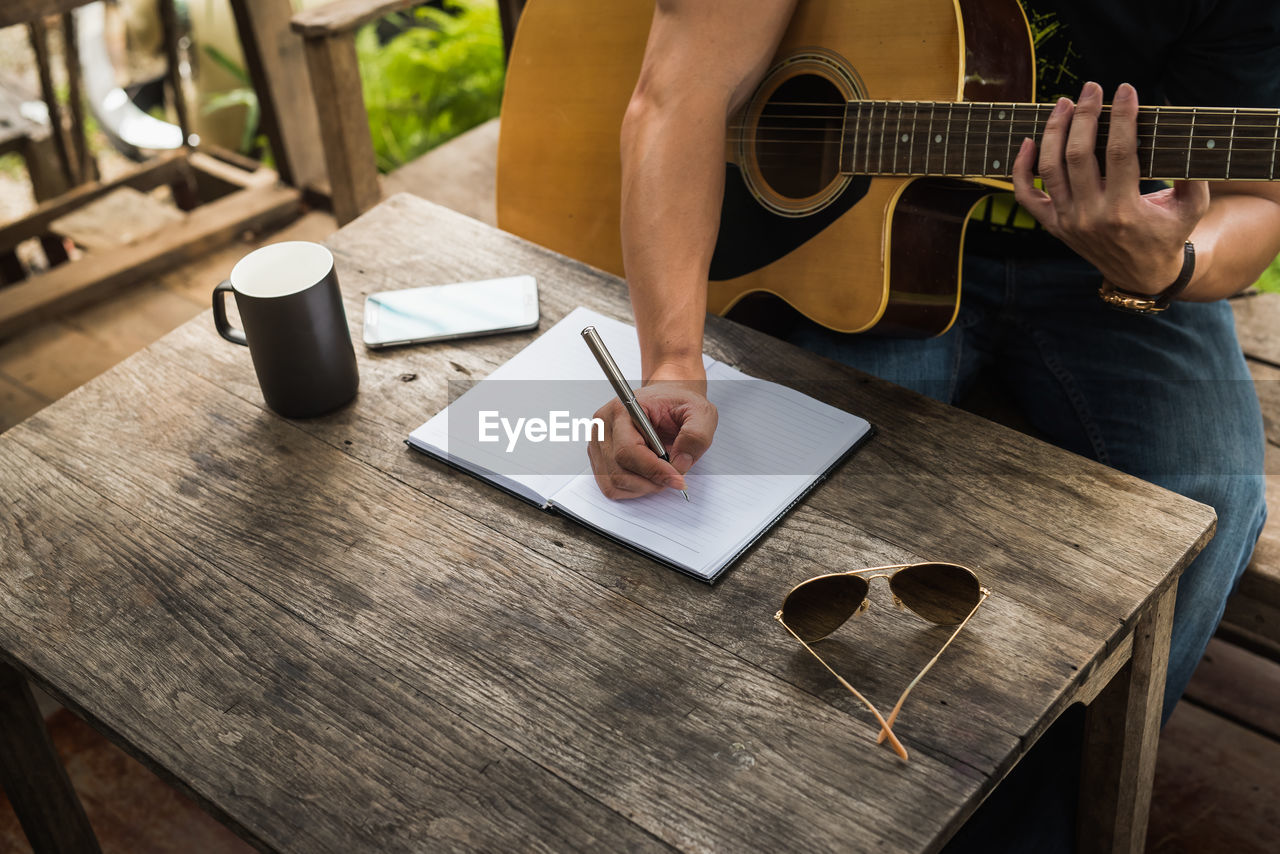 Midsection Of Man Writing While Playing Guitar In Balcony