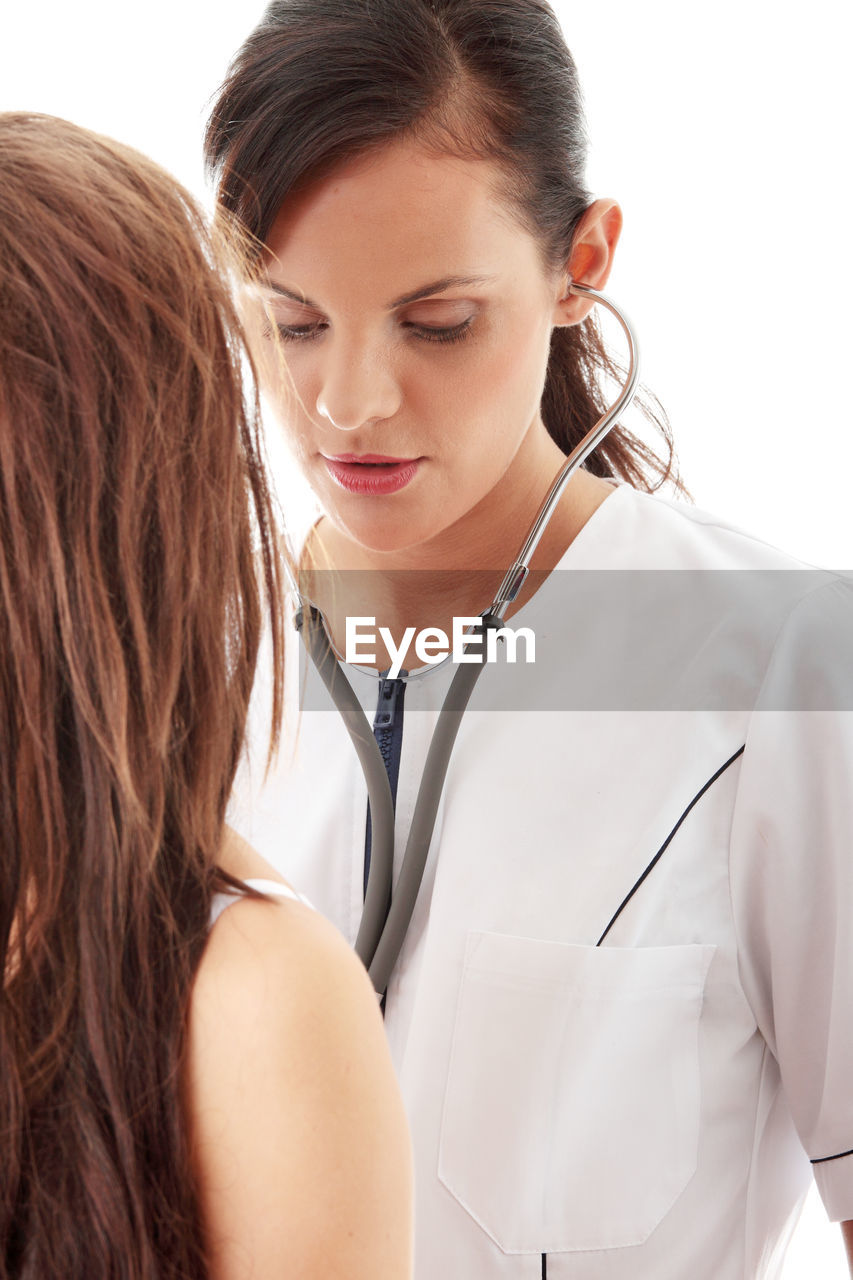 Doctor examining young woman against white background