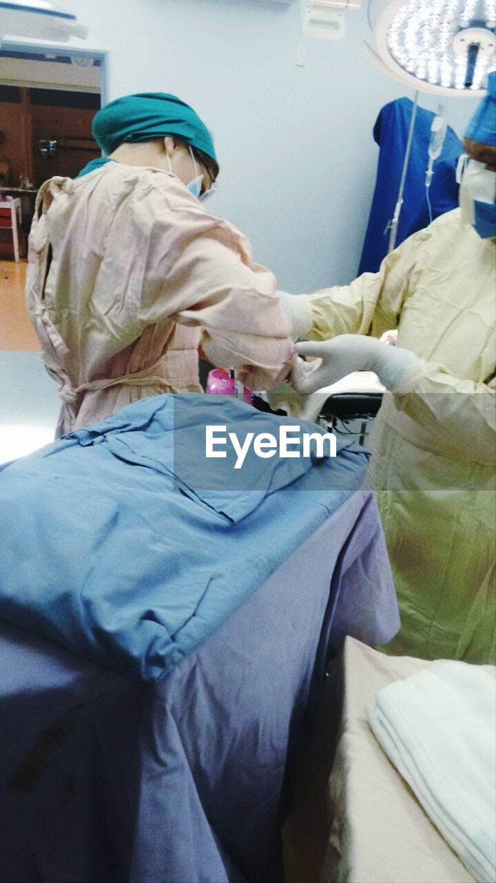 rear view, healthcare and medicine, indoors, hospital, bed, surgical glove, surgical mask, surgeon, human hand, mammal, day