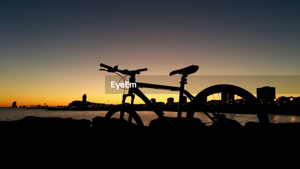 sky, sunset, silhouette, copy space, clear sky, water, nature, bicycle, transportation, architecture, sea, outdoors, land, built structure, orange color, beach, no people, mode of transportation, land vehicle