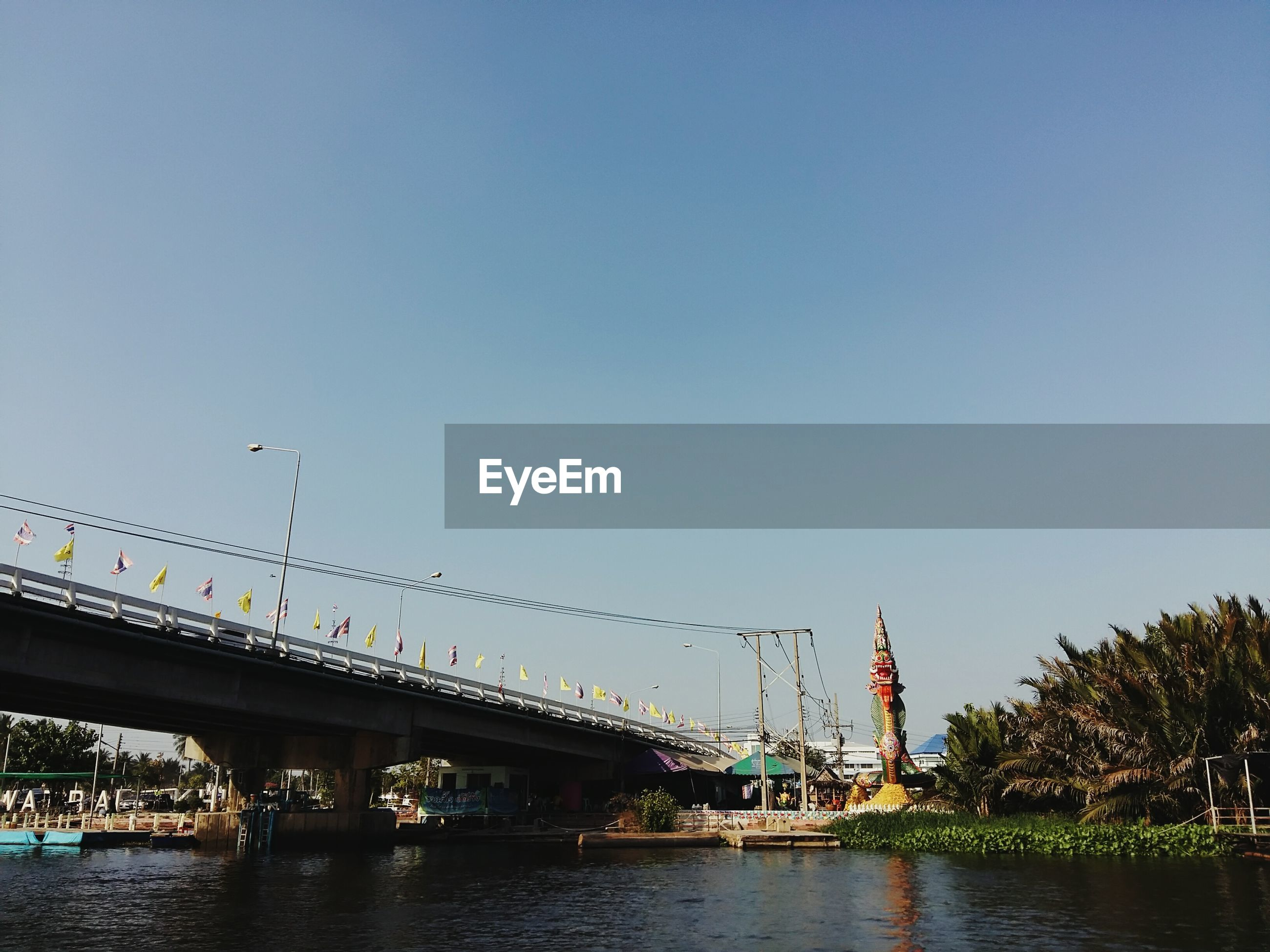 water, clear sky, connection, transportation, bridge - man made structure, built structure, architecture, waterfront, river, copy space, bridge, mode of transport, reflection, sky, bird, engineering, building exterior, outdoors, nautical vessel, tree