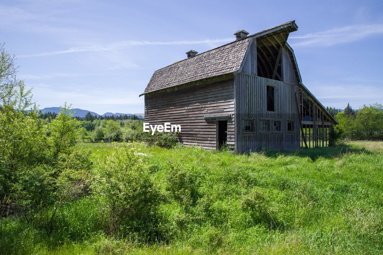 Old wooden barn on grassy field against sky