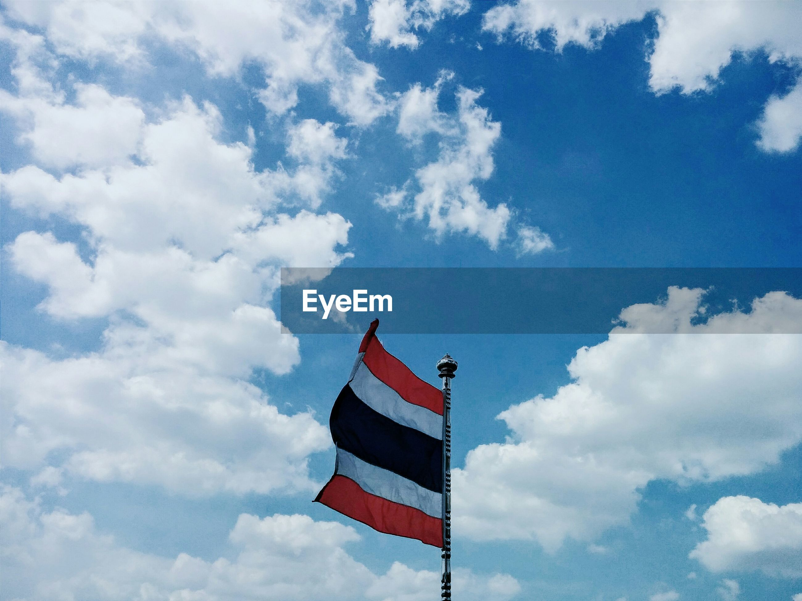 Low angle view of thai flag against cloudy sky
