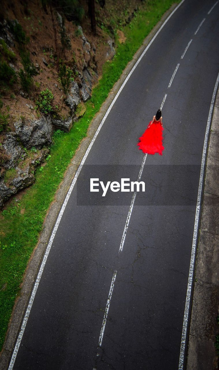 High angle view of woman wearing red dress on country road