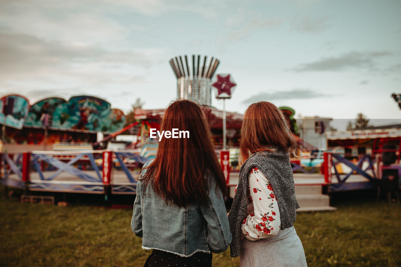 Rear View Of Women Standing At Amusement Park Against Sky