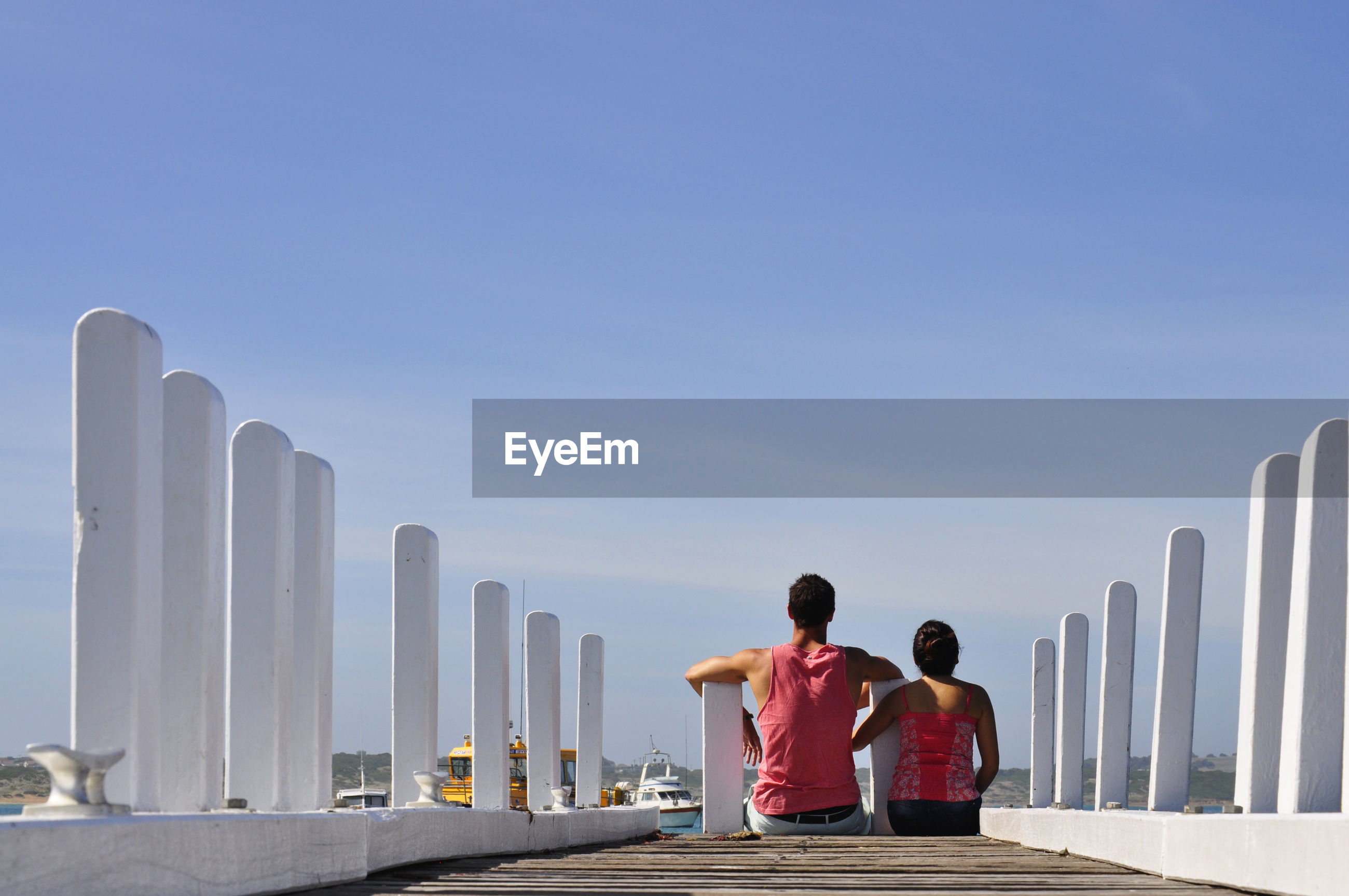 Rear view of couple sitting on pier against sky