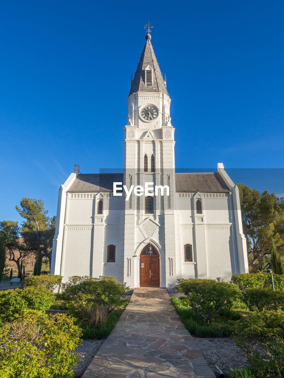 View Of White Dutch Reformed Church Against Blue Sky, Nieu-Bethesda, South Africa