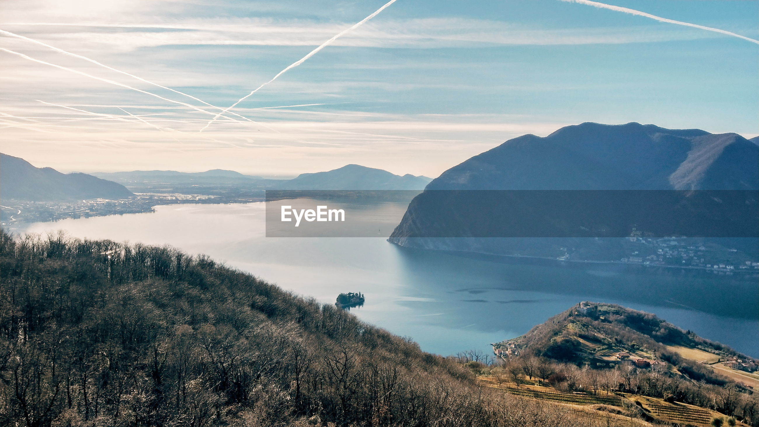 SCENIC VIEW OF SEA AND MOUNTAINS AGAINST VAPOR TRAILS IN SKY