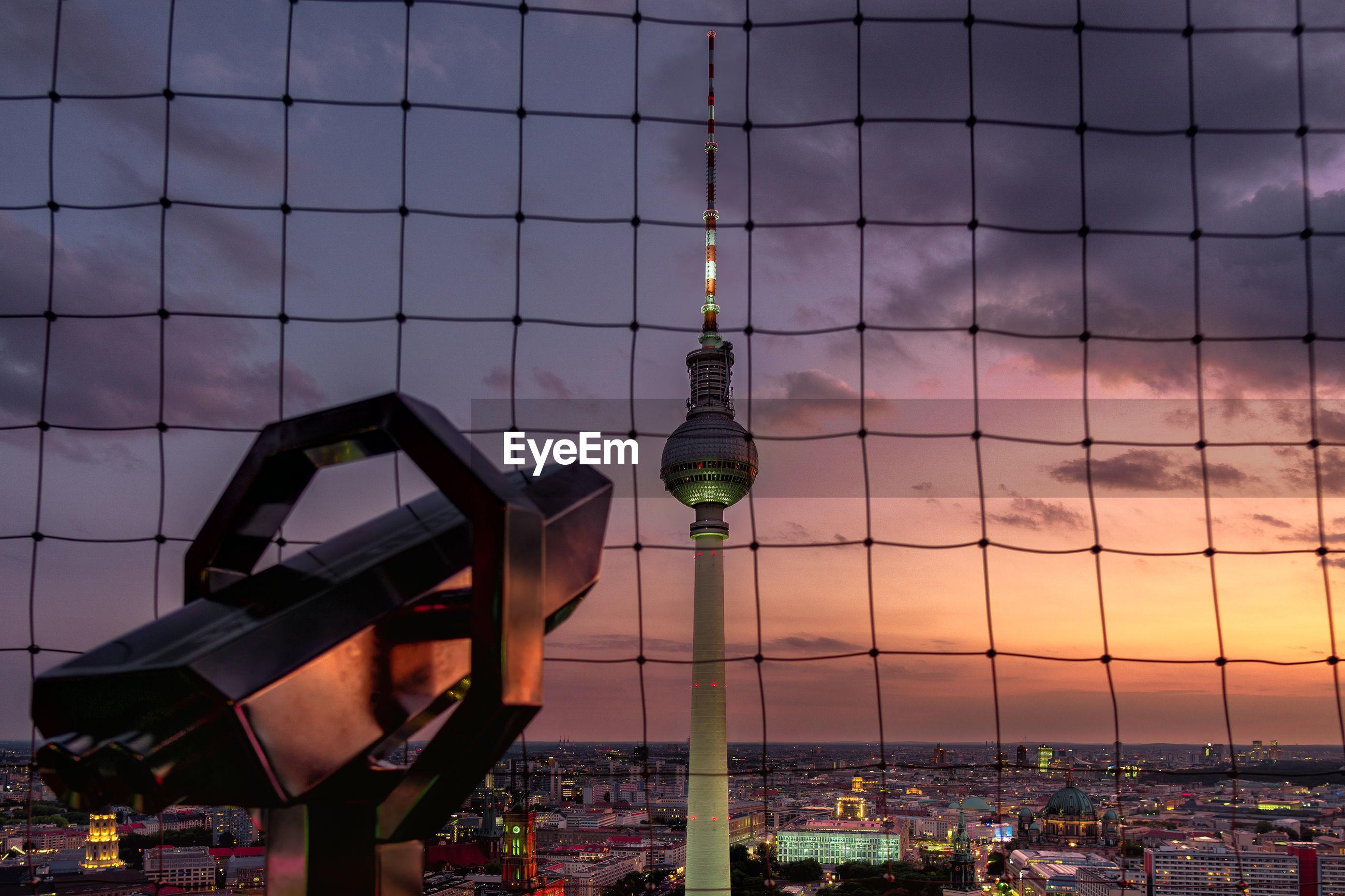 Fernsehturm seen through netting during sunset