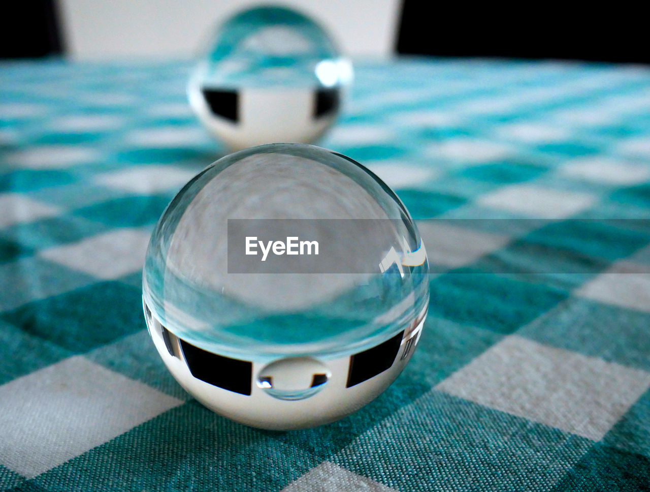 close-up, sphere, still life, crystal ball, table, ball, indoors, reflection, focus on foreground, no people, glass - material, selective focus, pattern, day, high angle view, transparent, shape, design, tablecloth, single object, silver colored, electric lamp, clean