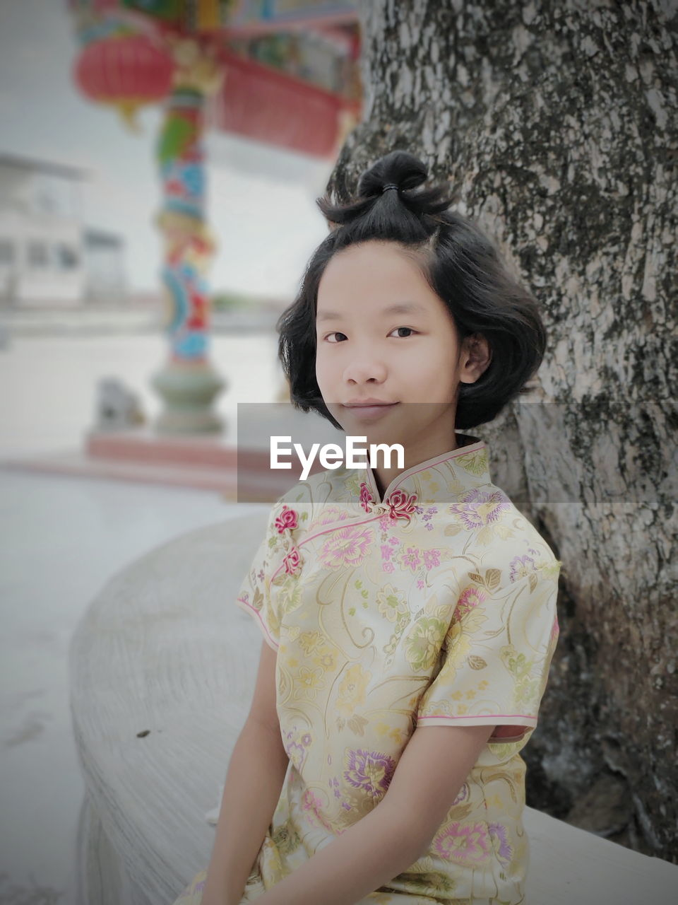 Portrait Of Cute Girl Sitting Against Tree Trunk