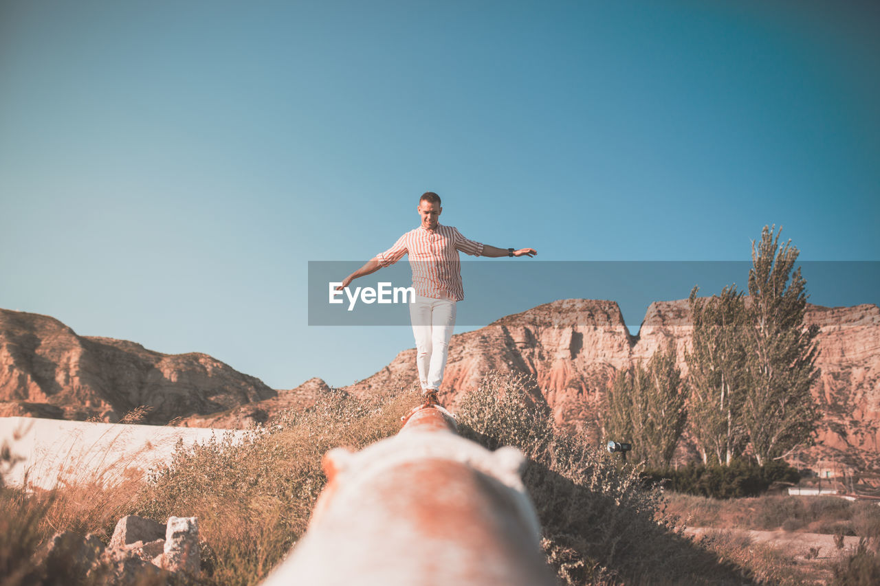 Man Walking On Railing Against Sky