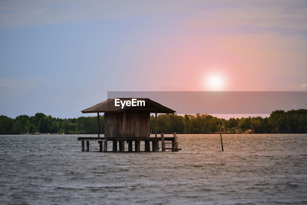 water, built structure, stilt, sunset, architecture, sky, waterfront, no people, lake, tranquility, nature, tree, outdoors, beauty in nature, scenics, day
