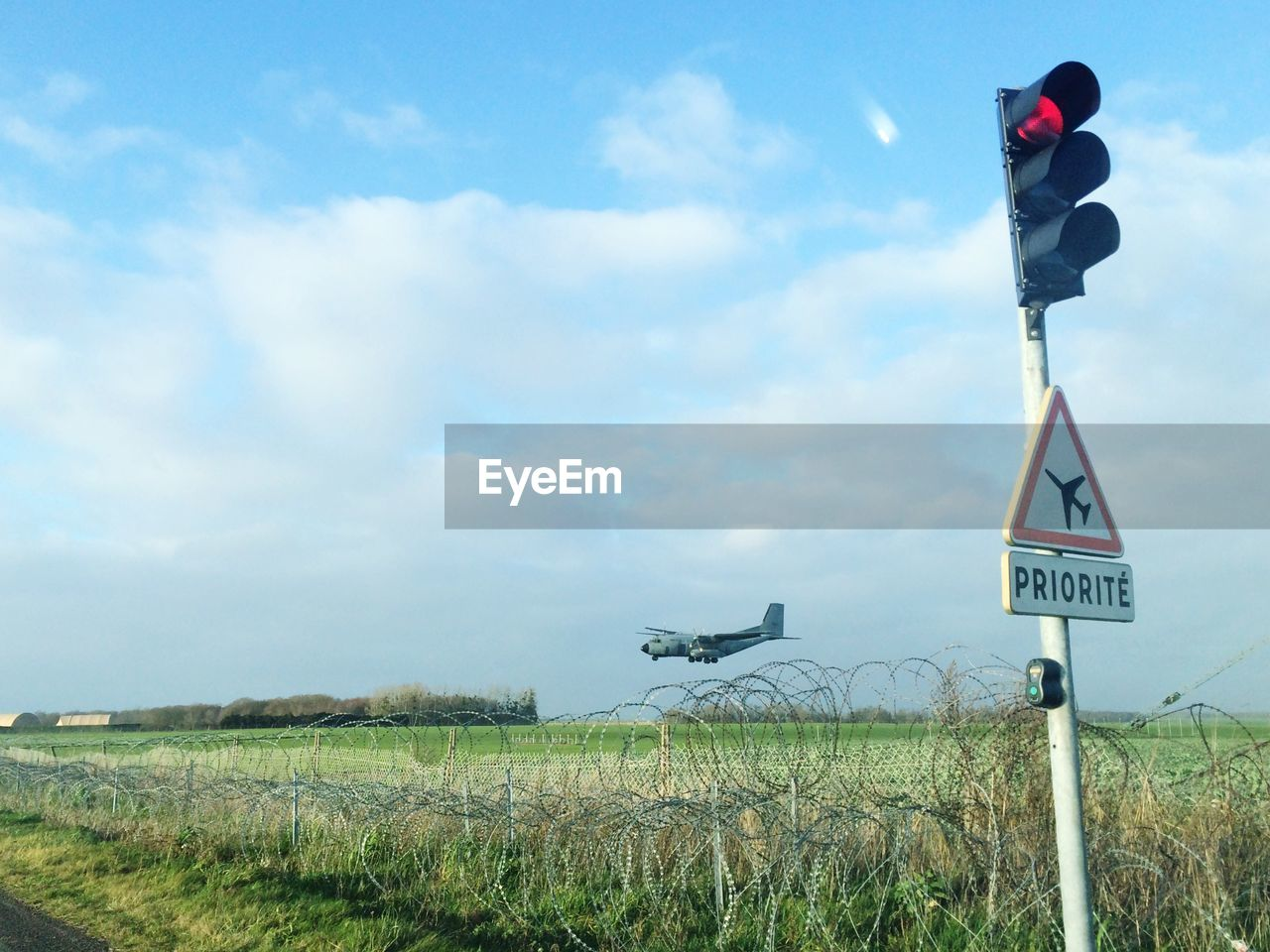 communication, road sign, safety, warning sign, guidance, sky, danger, day, cloud - sky, text, field, no people, outdoors, low angle view, grass, nature