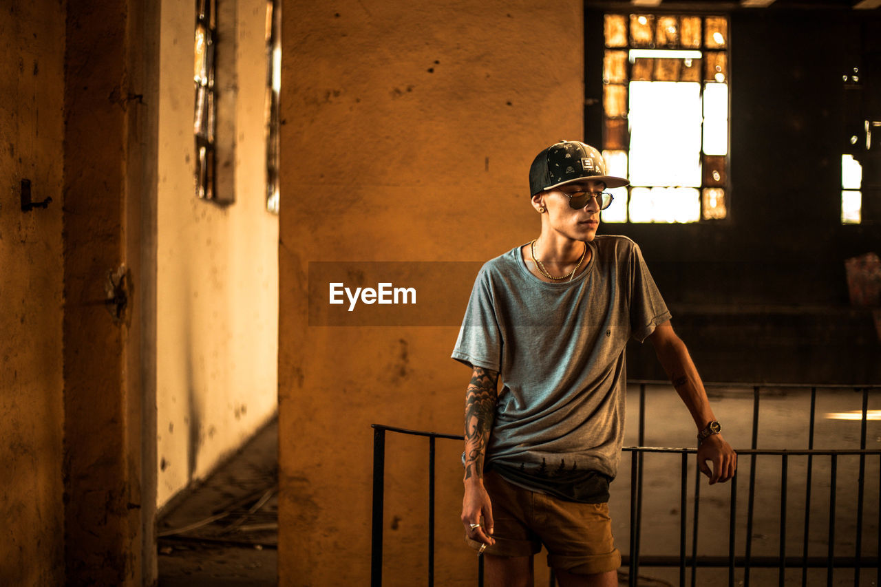 one person, three quarter length, real people, young adult, young men, casual clothing, architecture, front view, standing, lifestyles, indoors, leisure activity, hat, men, clothing, focus on foreground, built structure, glasses