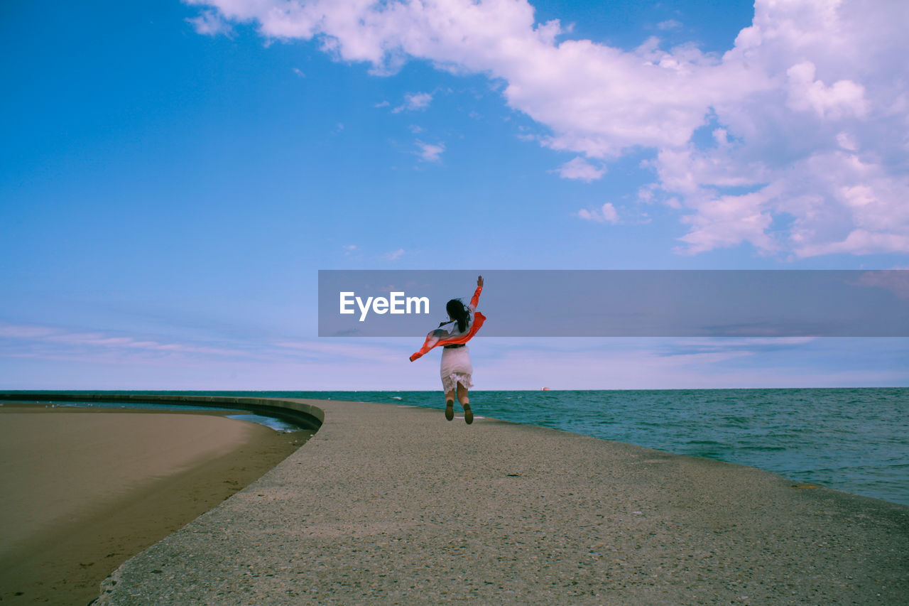 Rear view of woman walking on pier by sea against sky