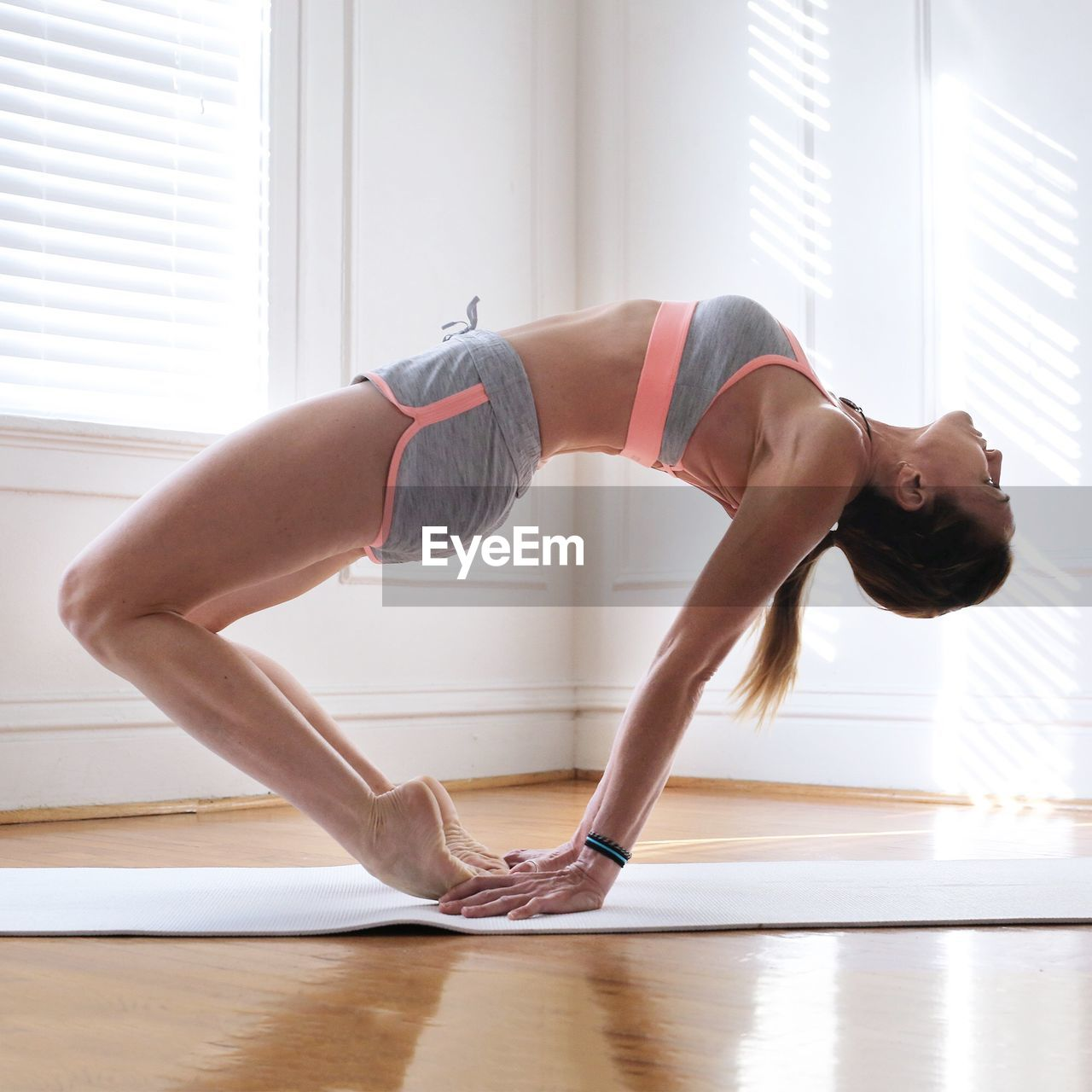 Side View Of Young Woman Doing Yoga At Studio