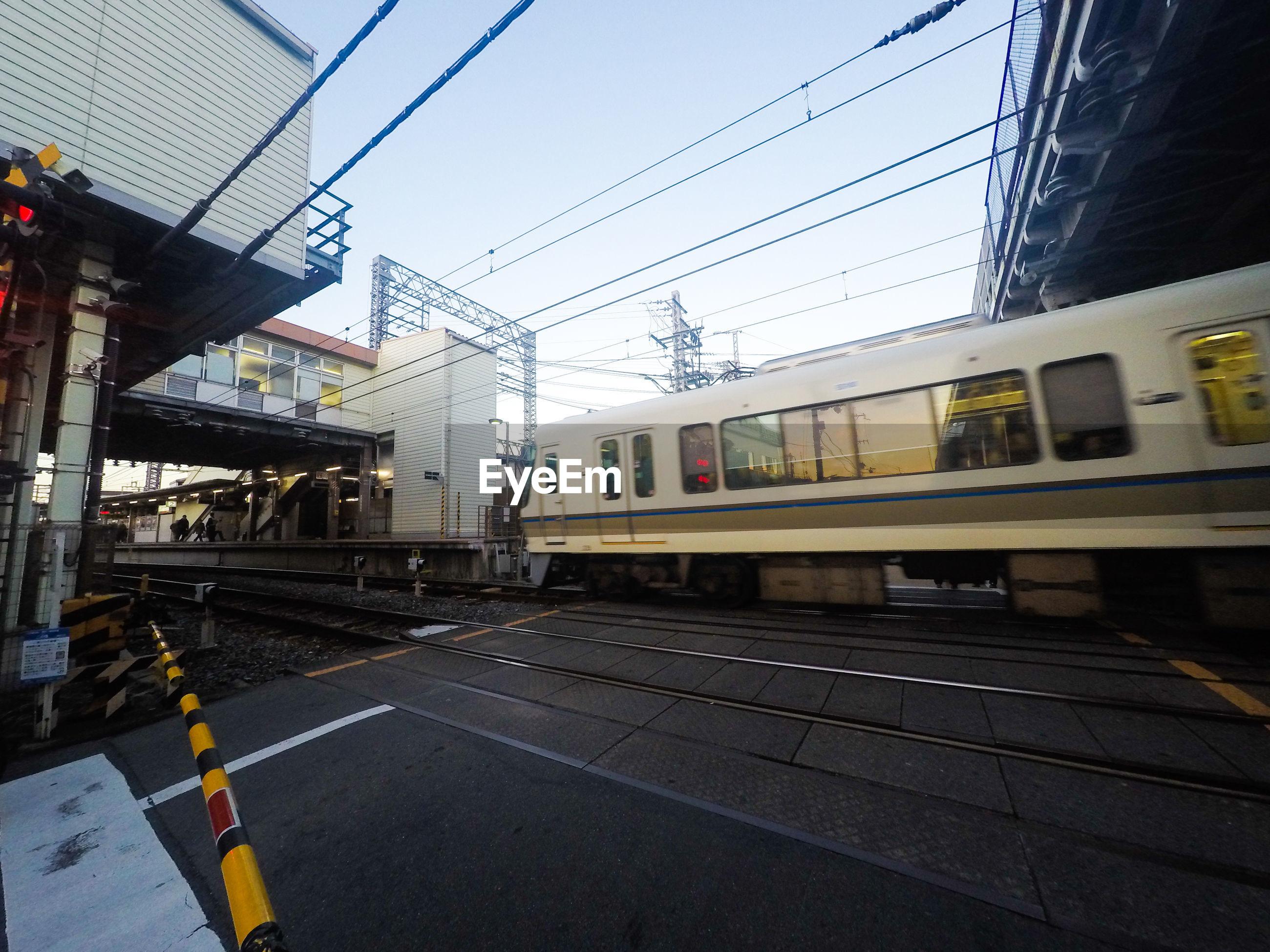 Railroad tracks on city street against sky
