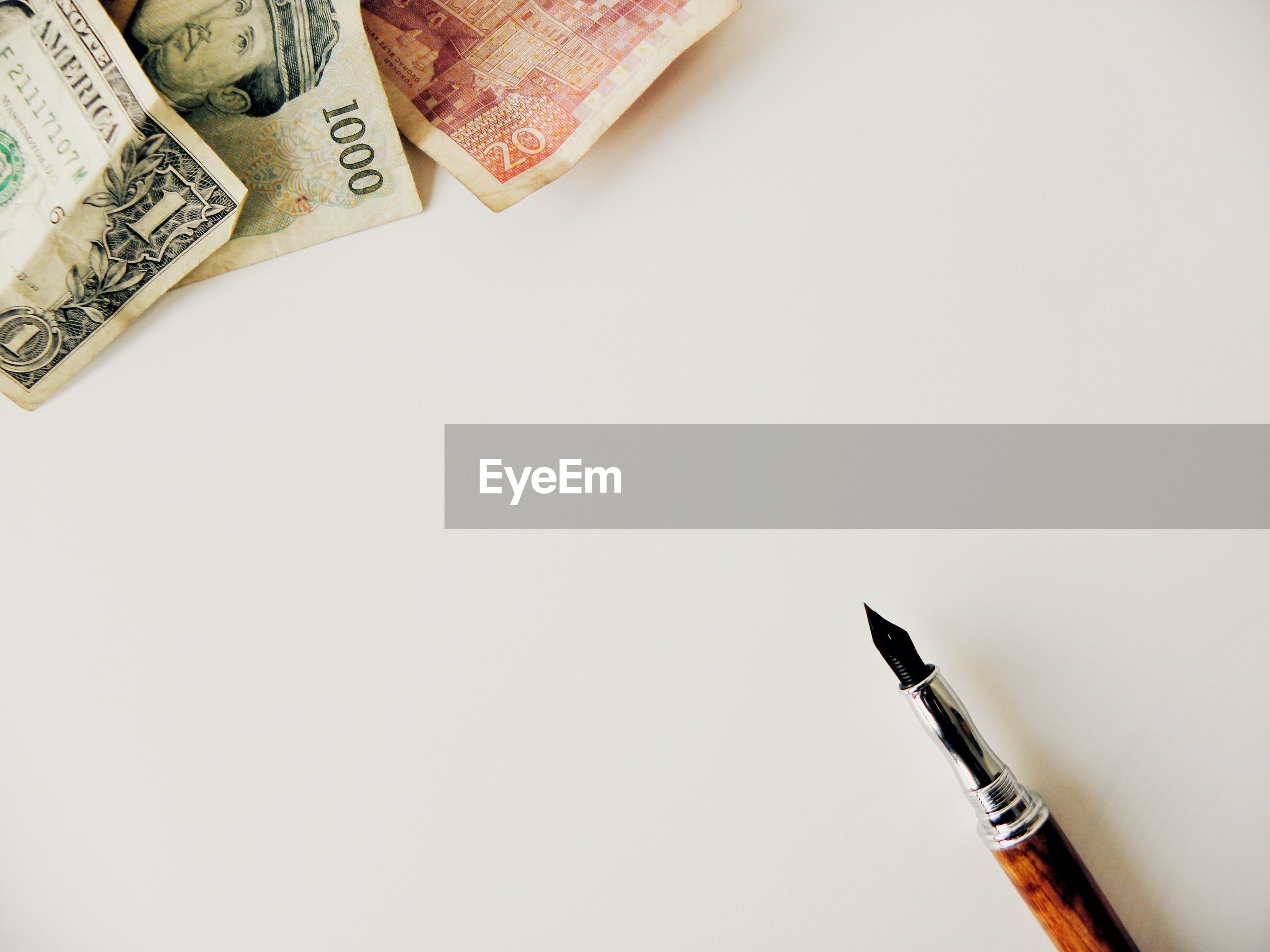 Close-up of pen and money over white background