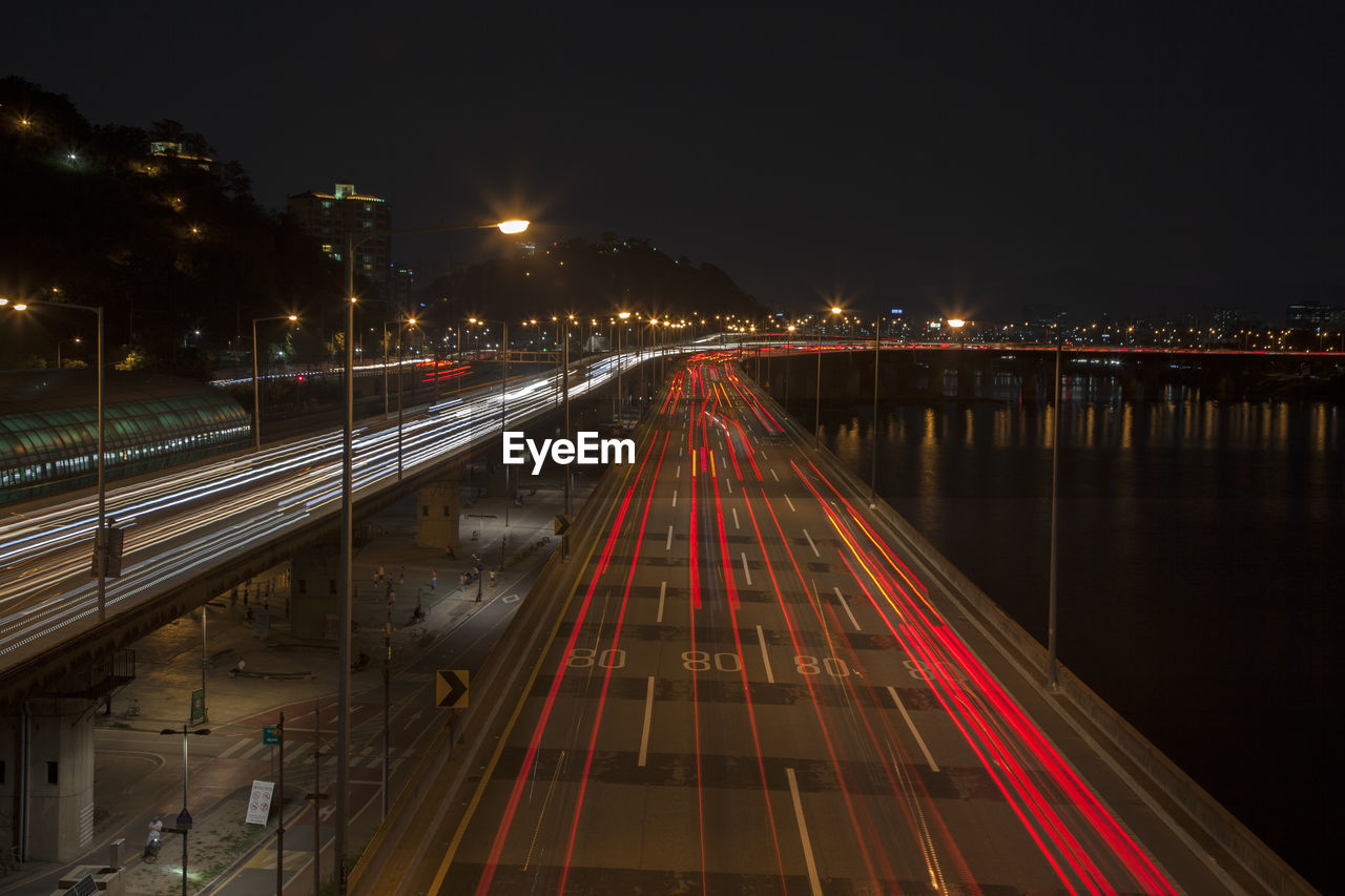 High Angle View Of Light Trails On Bridge And Street By River