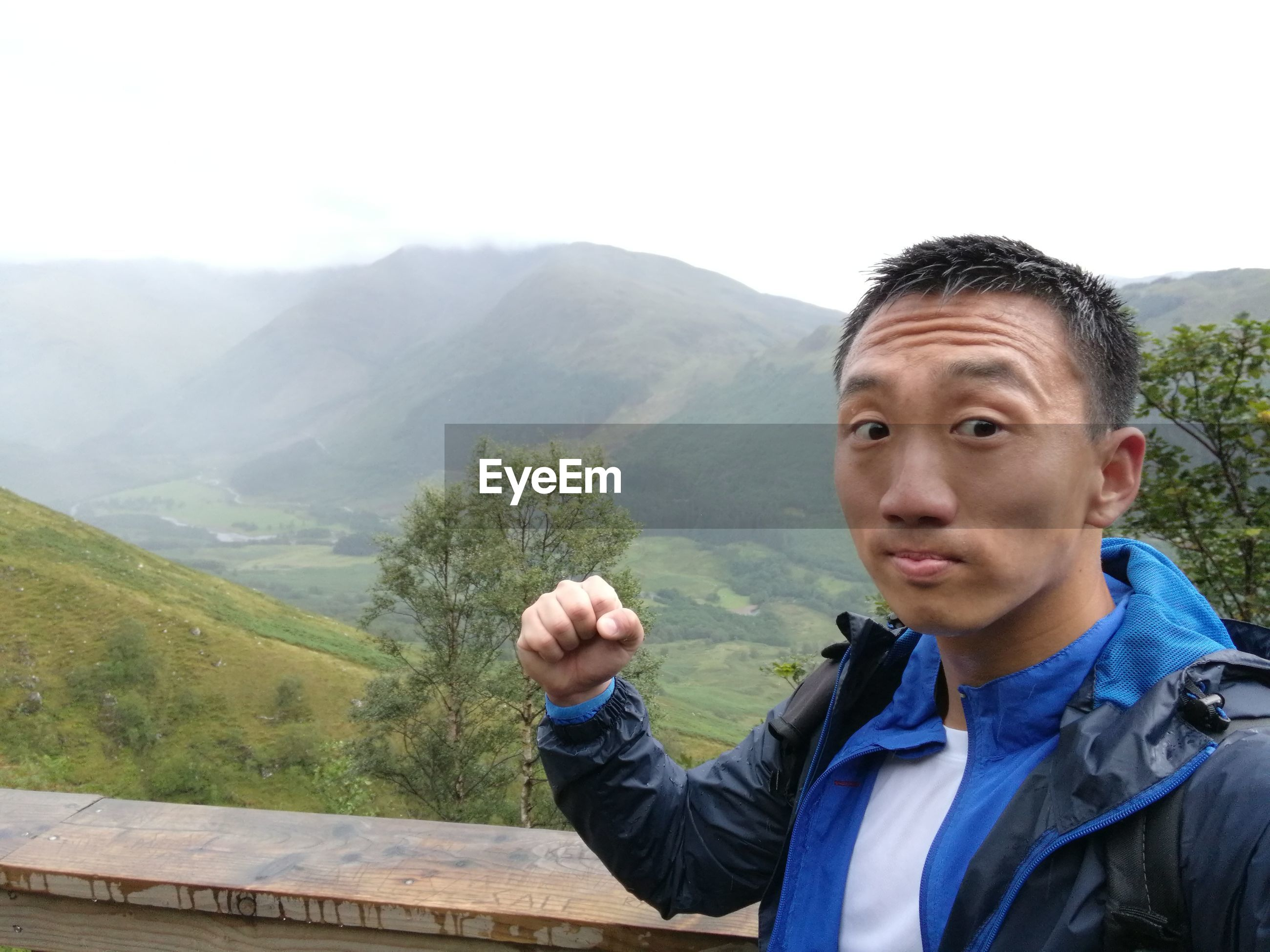 Portrait of young man clenching fist on mountains against sky