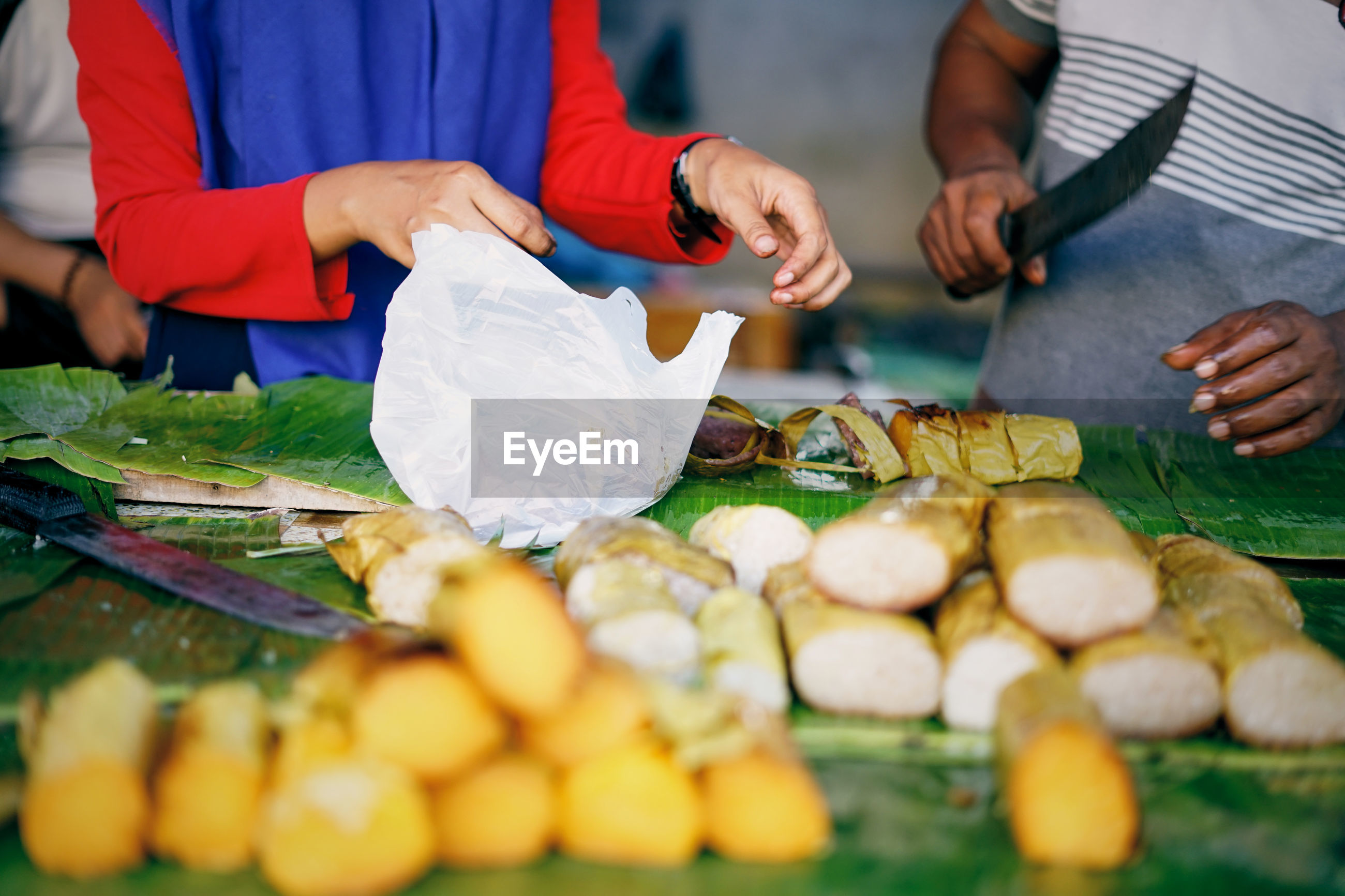 HIGH ANGLE VIEW OF PEOPLE PREPARING FOOD IN MARKET