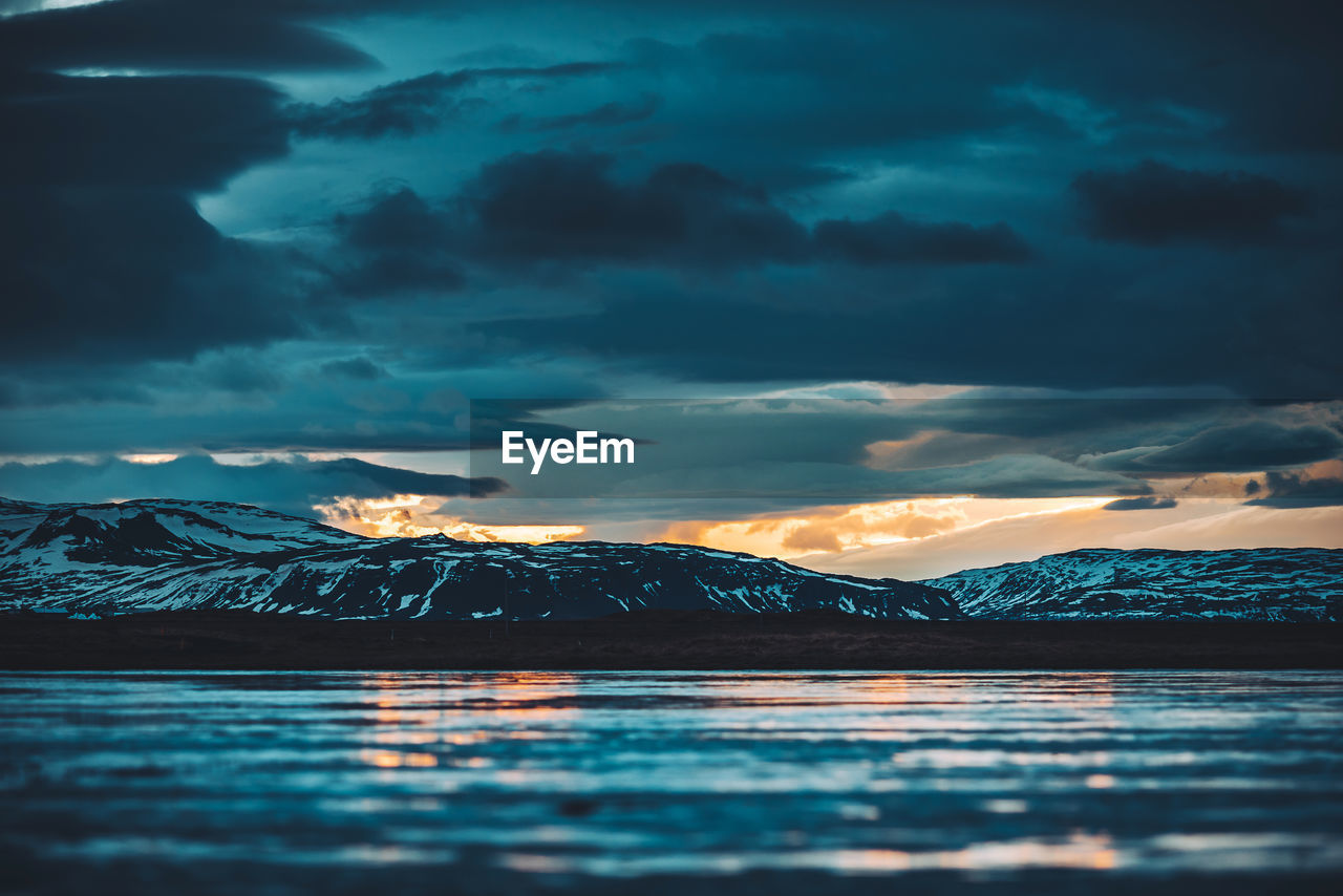 cloud - sky, sky, scenics - nature, beauty in nature, sunset, water, tranquil scene, tranquility, mountain, nature, no people, waterfront, non-urban scene, reflection, dramatic sky, cold temperature, idyllic, winter, outdoors, snowcapped mountain