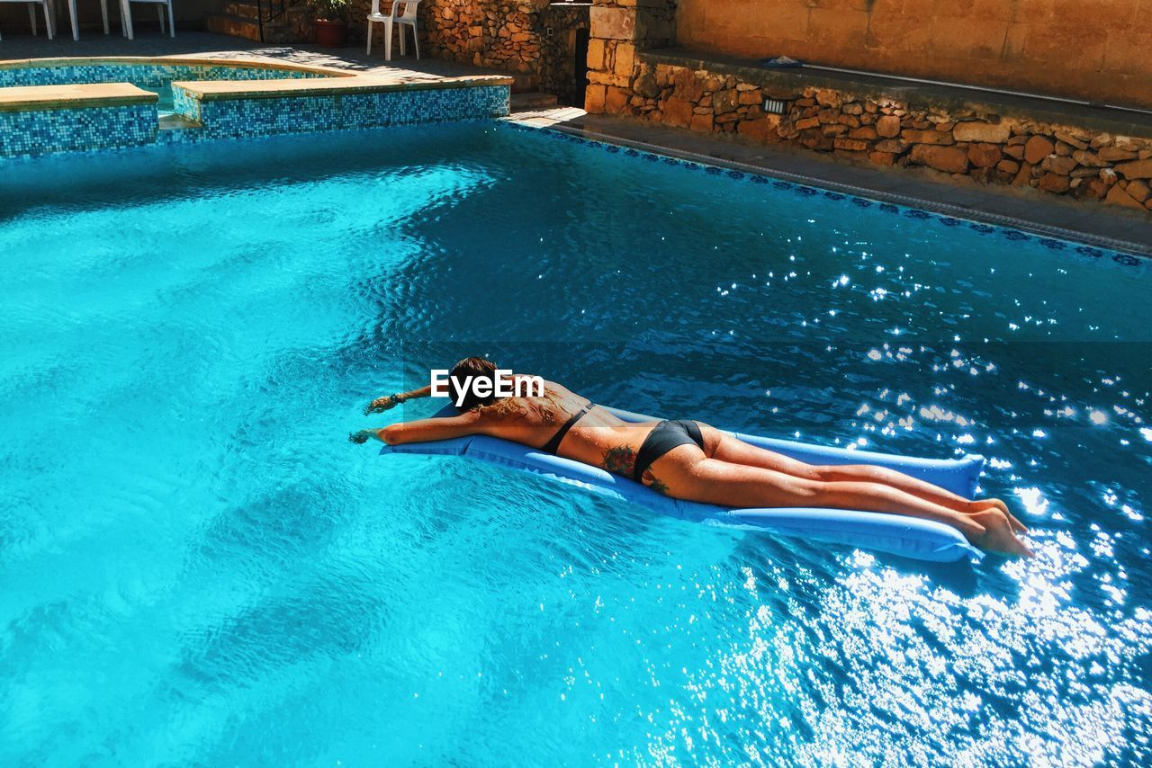 High Angle View Of Sensuous Woman In Bikini Relaxing On Raft At Swimming Pool