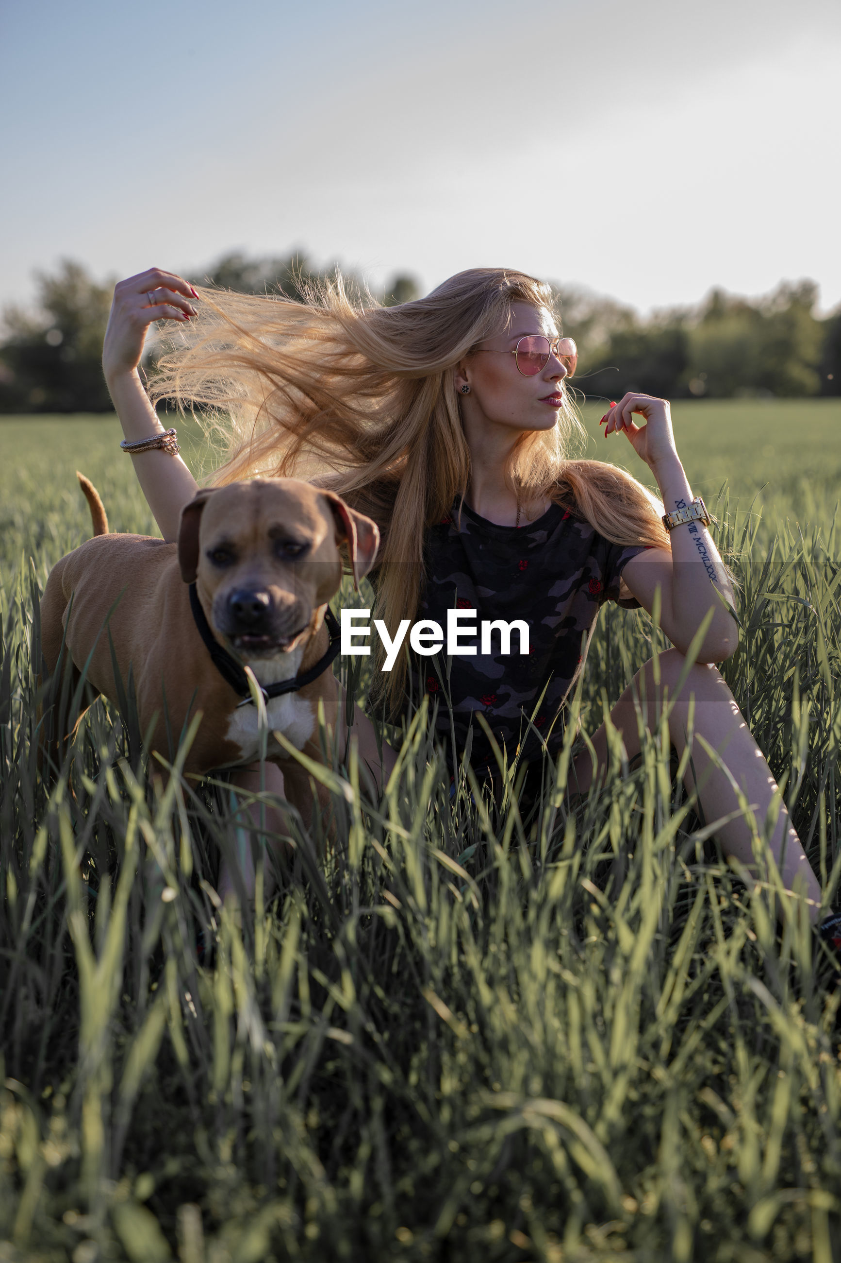 Woman with dog on field against sky