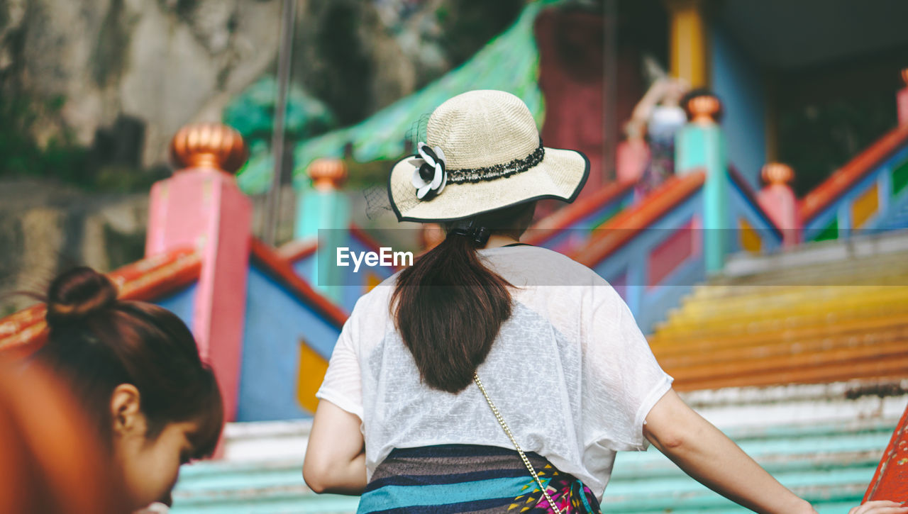 REAR VIEW OF PEOPLE SITTING ON AMUSEMENT PARK