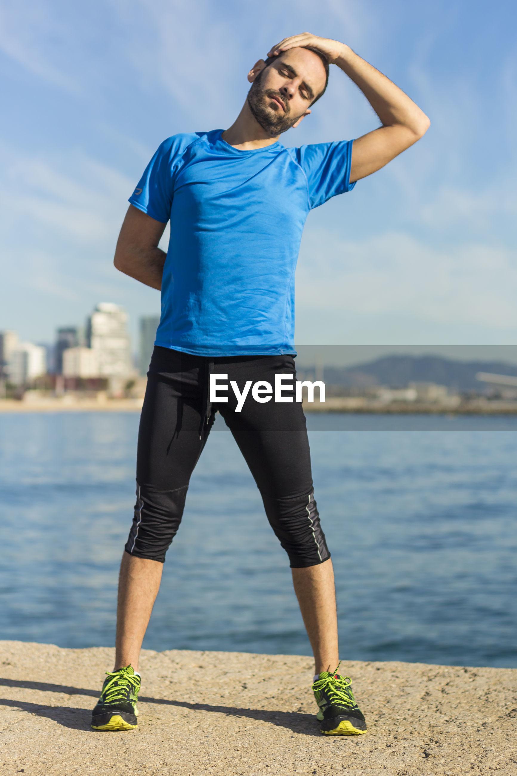 Man exercising against sea at beach