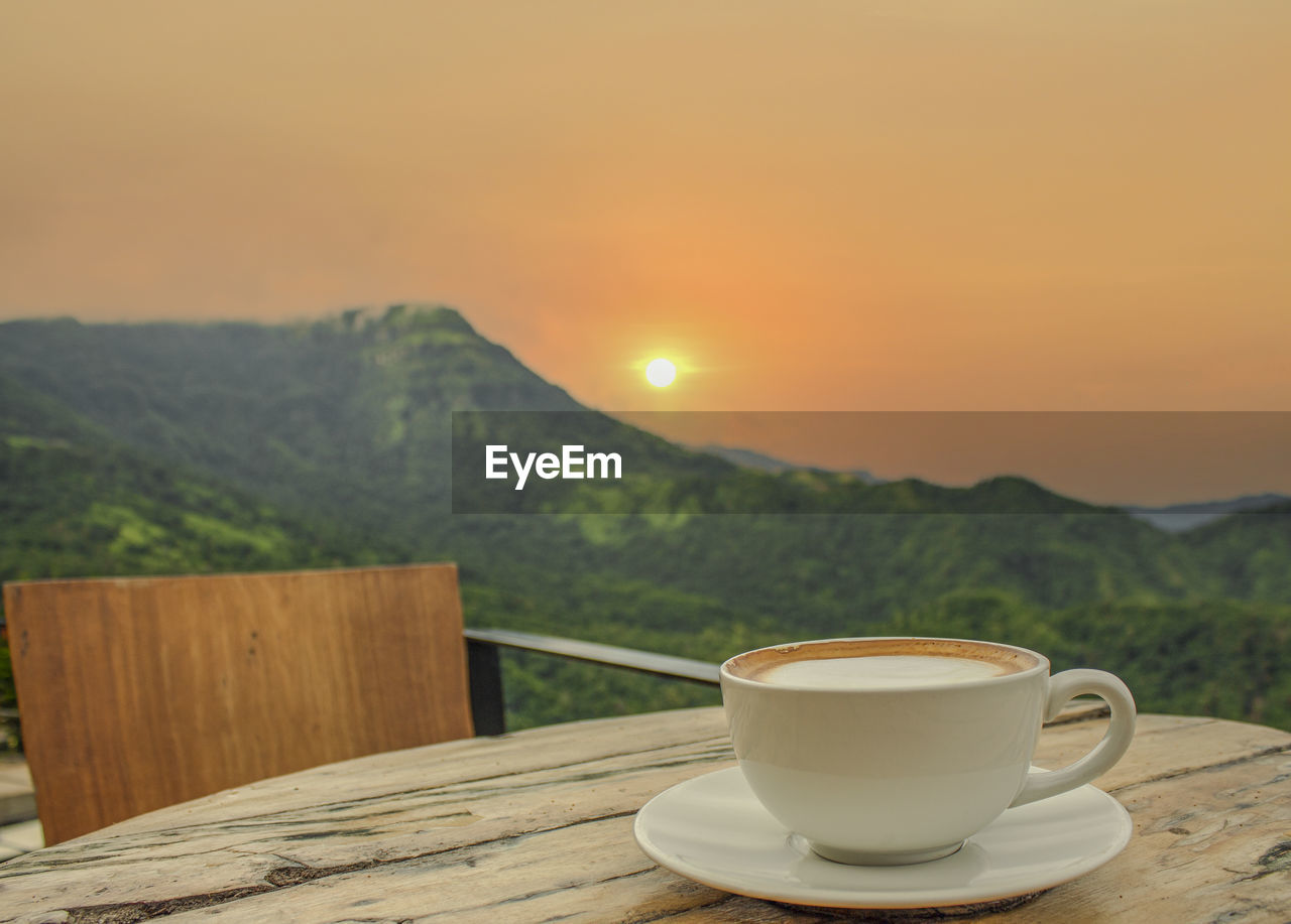 COFFEE CUP ON TABLE AGAINST ORANGE SKY