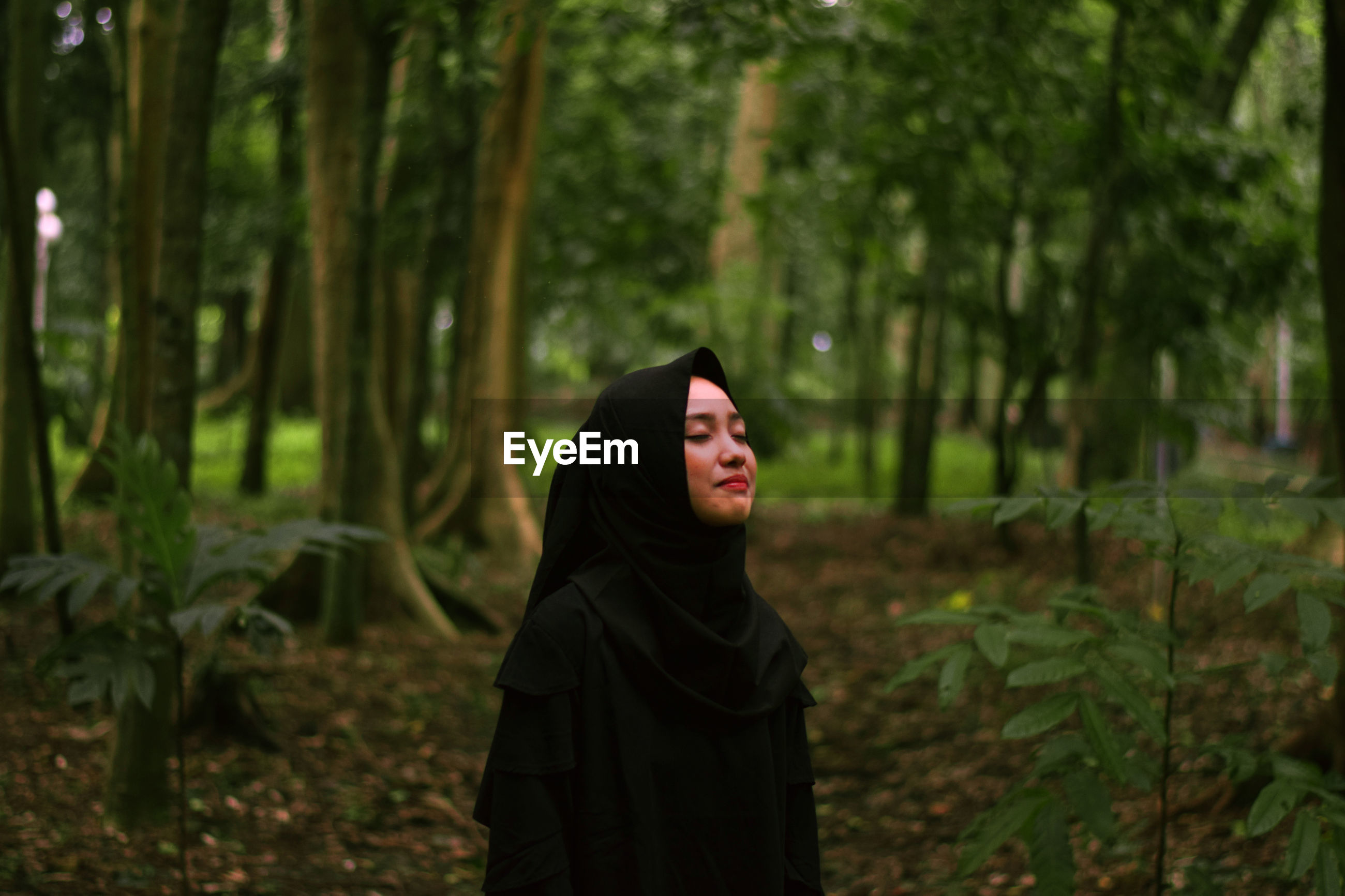 Woman with eyes closed standing against trees in forest