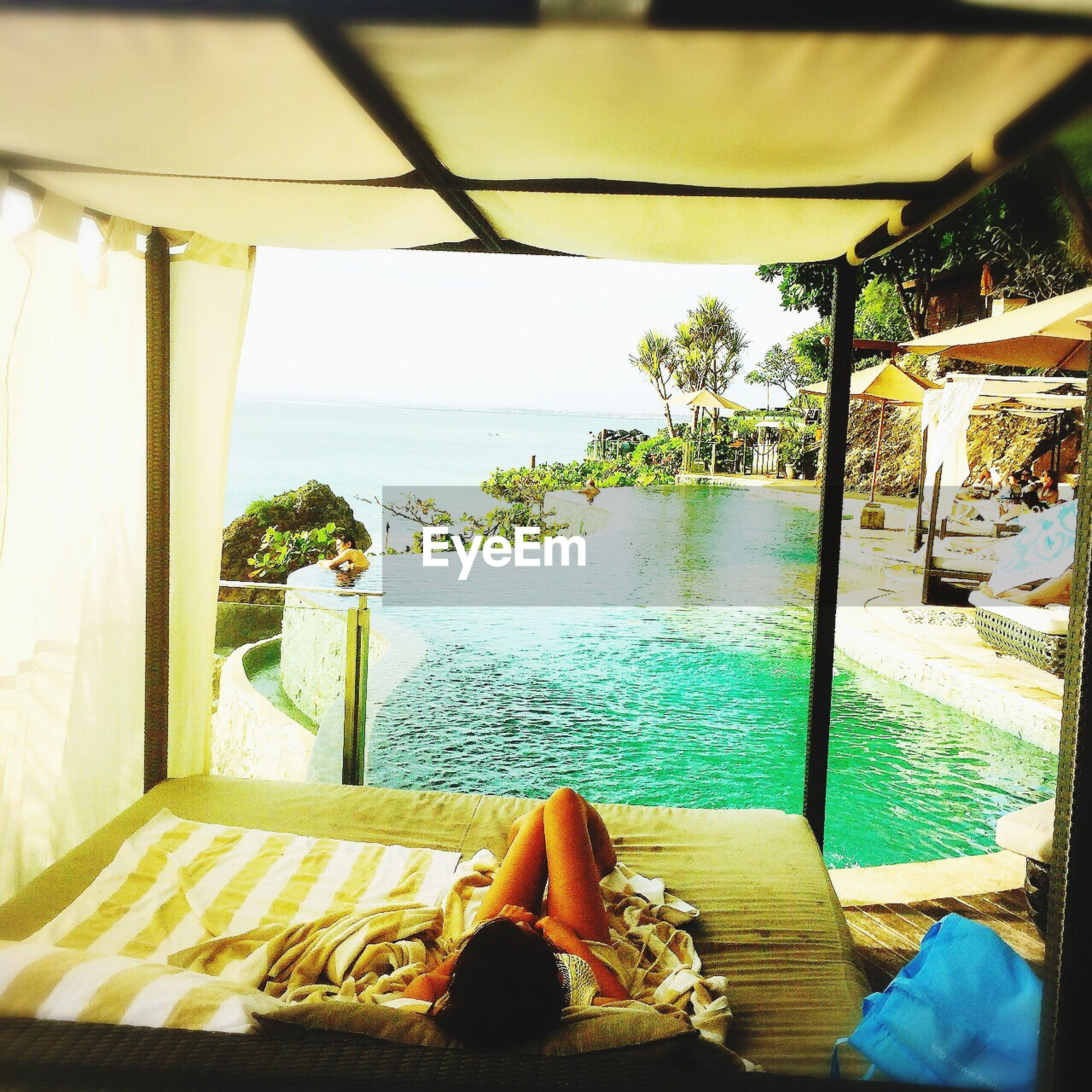 sea, water, sky, horizon over water, indoors, nature, tranquility, built structure, tranquil scene, beauty in nature, sunlight, scenics, day, table, swimming pool, beach, architecture, blue, house, potted plant