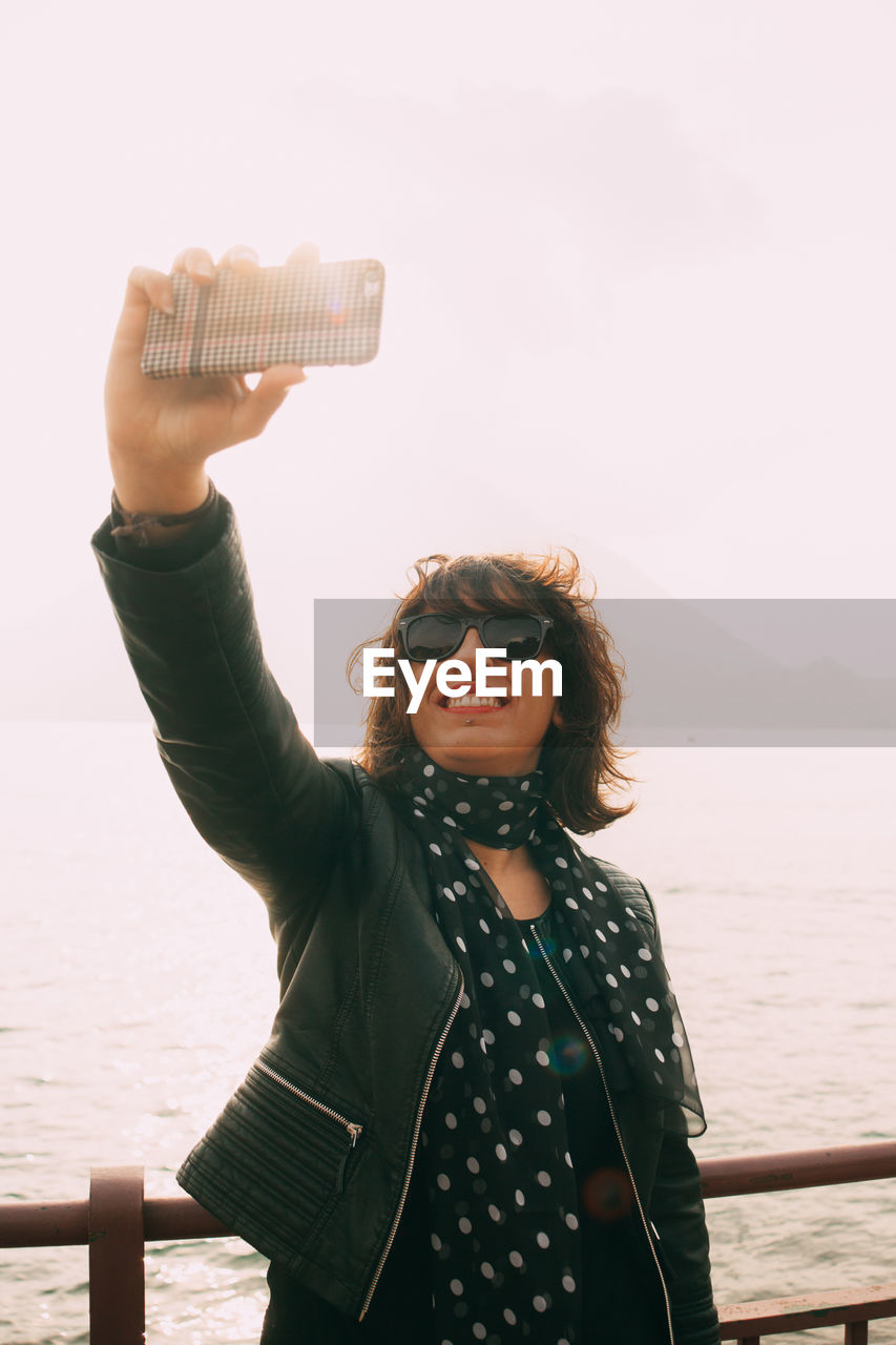 Smiling woman taking selfie by sea against clear sky
