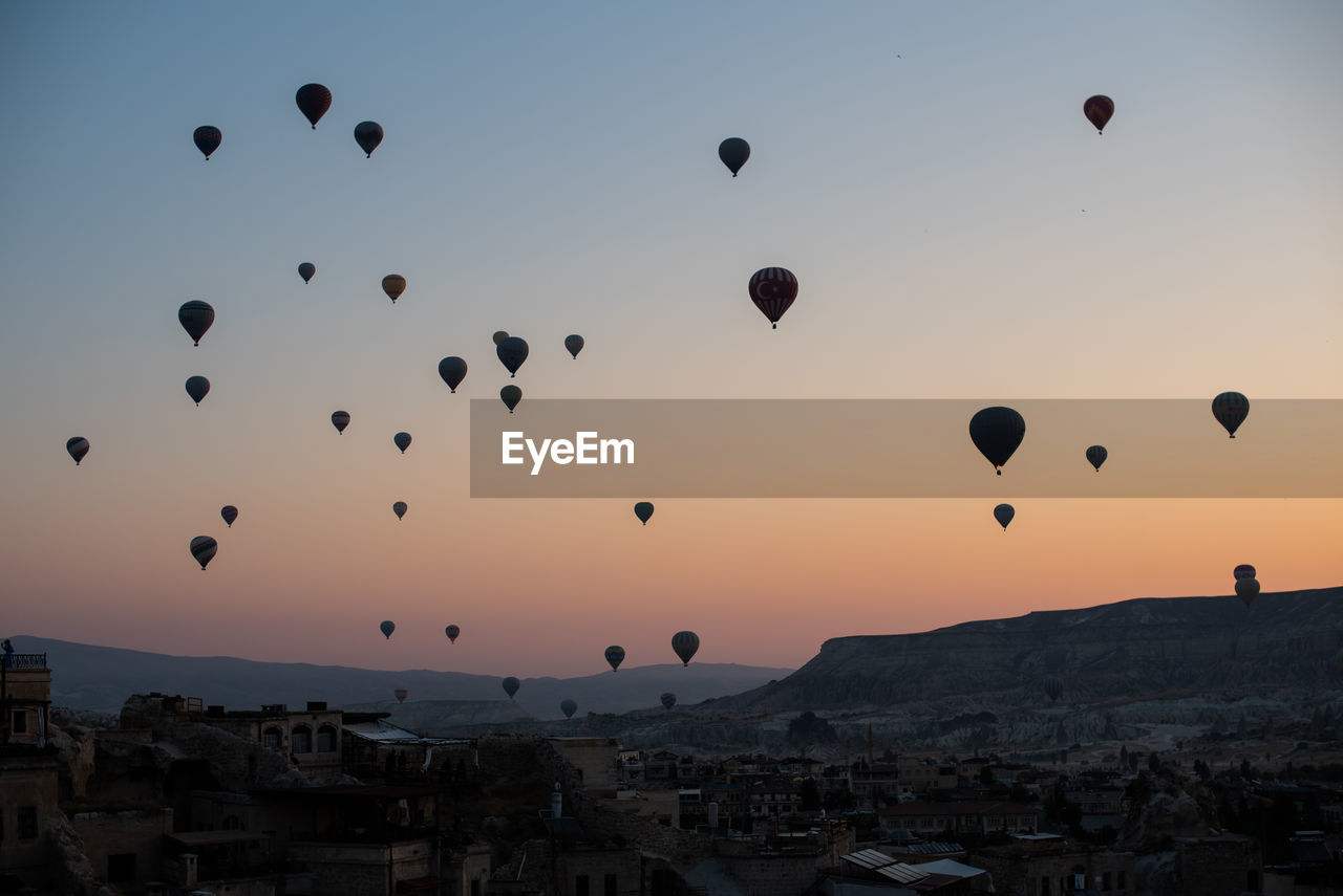 Hot Air Balloons Flying Over City Against Sky During Sunset