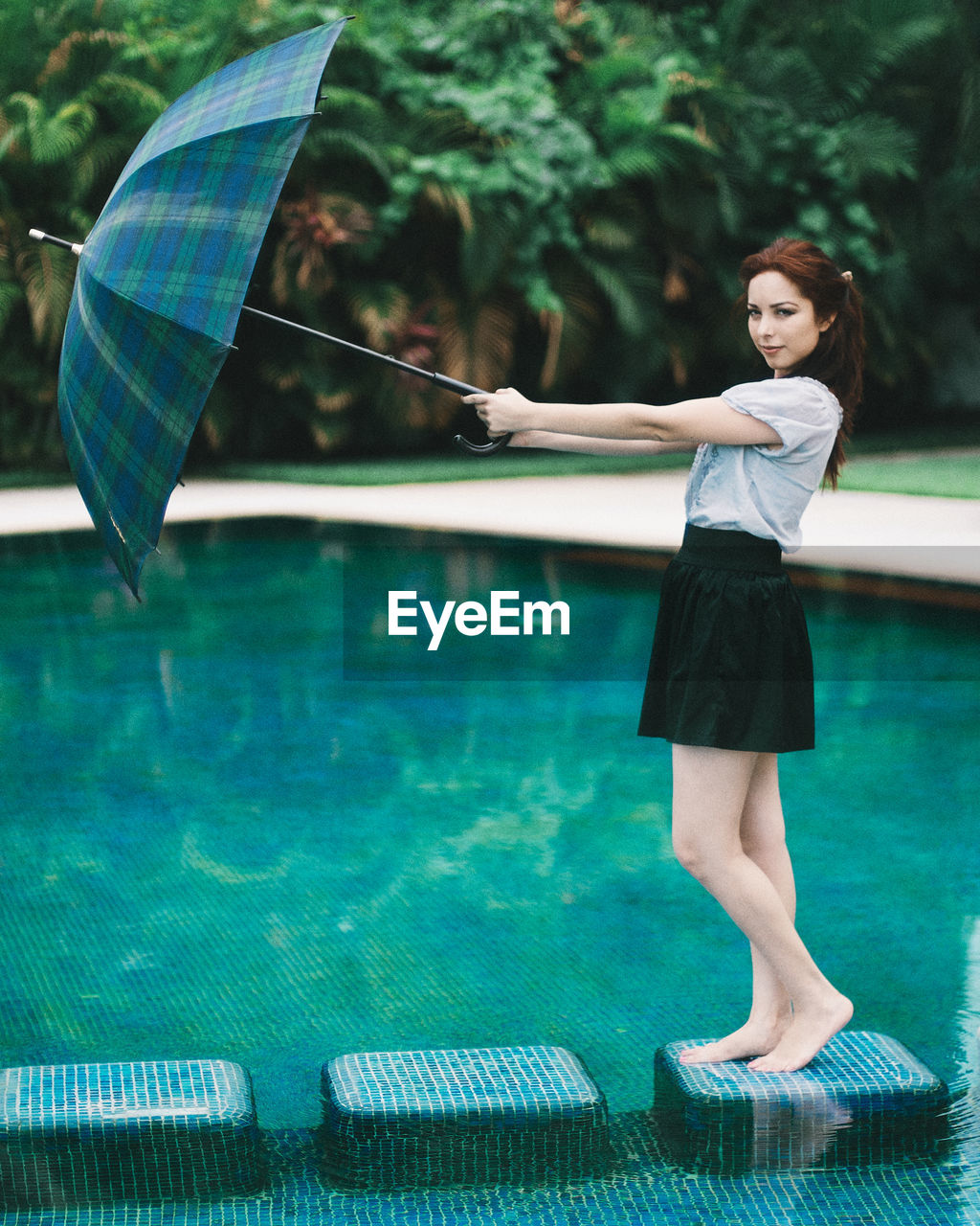 Young Woman Holding Umbrella Standing In Water