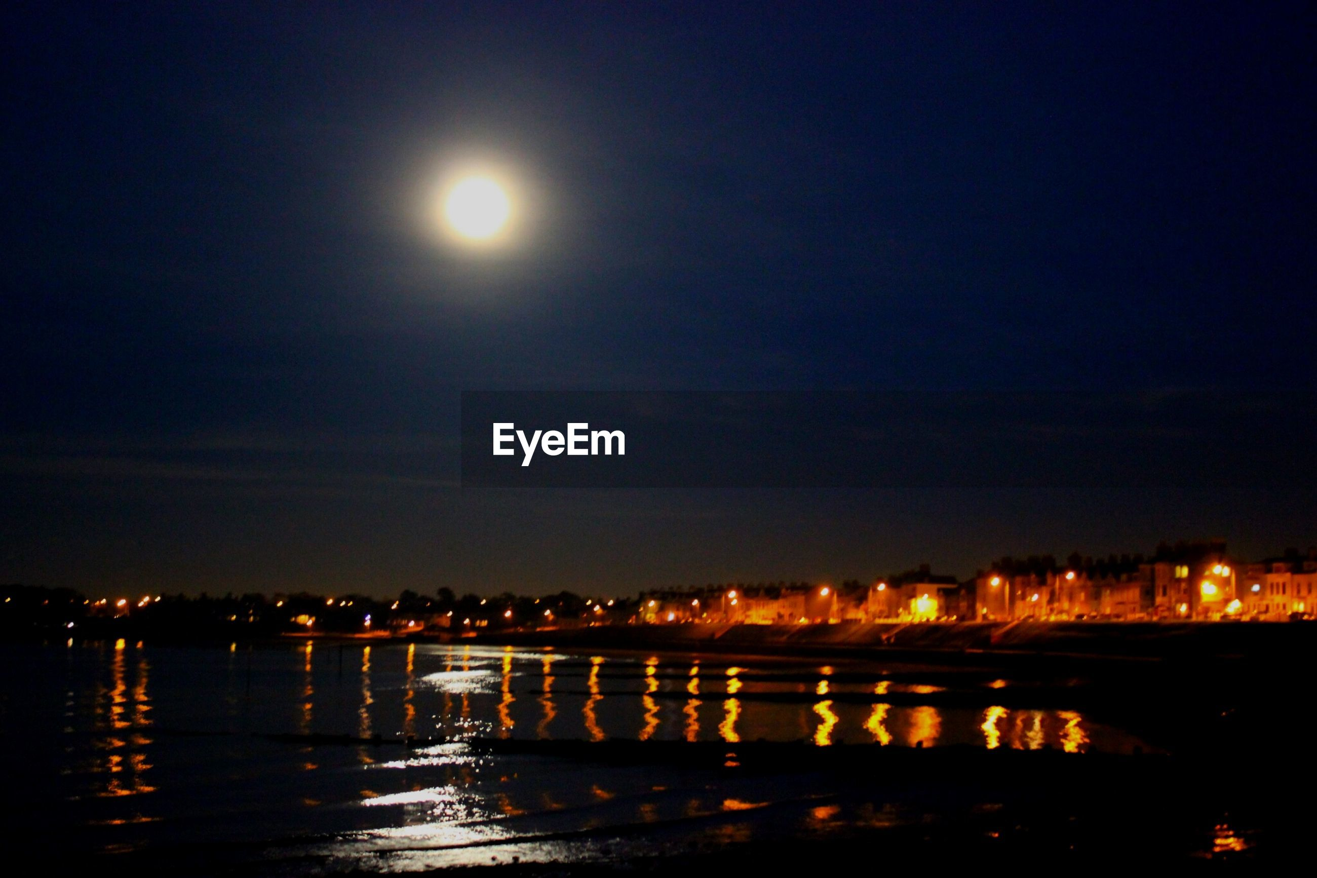 illuminated, night, water, waterfront, reflection, river, architecture, built structure, sky, sea, city, building exterior, connection, bridge - man made structure, moon, street light, lighting equipment, light, dusk, outdoors