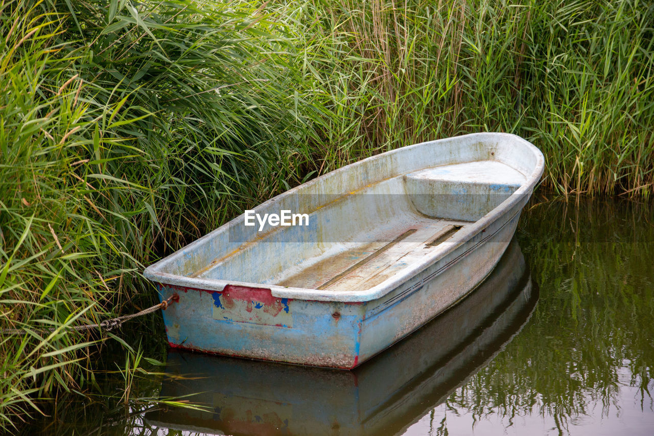 HIGH ANGLE VIEW OF ABANDONED BOAT ON GRASS