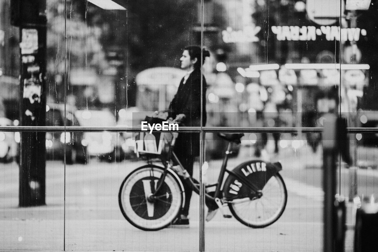 BICYCLE PARKED ON GLASS WINDOW