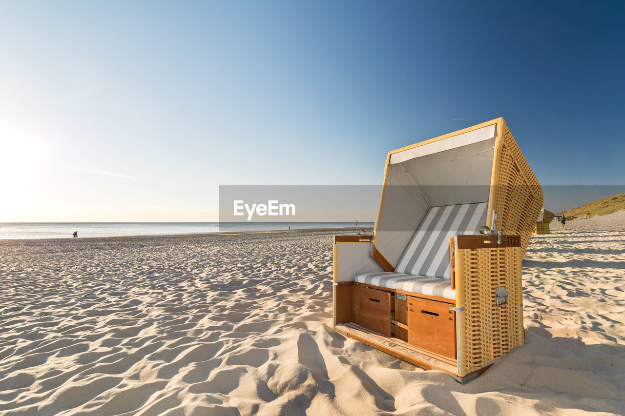 land, sky, beach, sand, sea, sunlight, nature, beauty in nature, scenics - nature, water, horizon, day, clear sky, tranquility, tranquil scene, horizon over water, no people, hooded beach chair, blue, outdoors