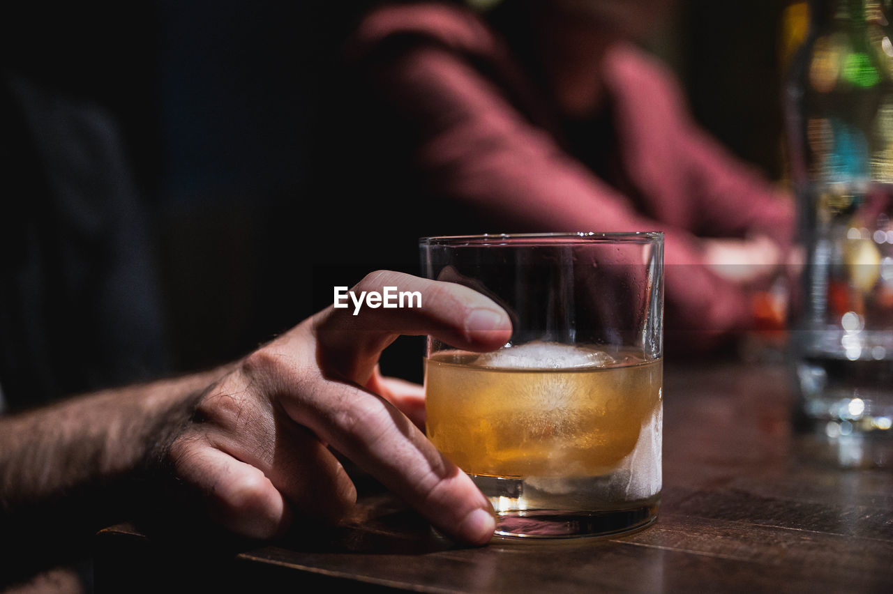 MIDSECTION OF MAN DRINKING GLASS IN BAR